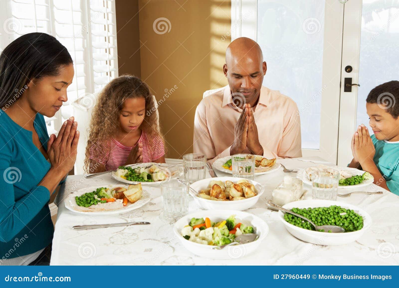Famille disant la grâce avant repas à la maison