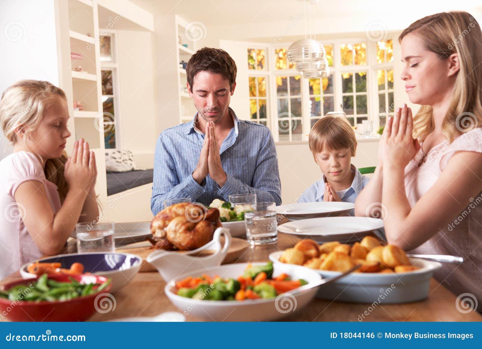 Famille disant la prière avant de manger le dîner de rôti
