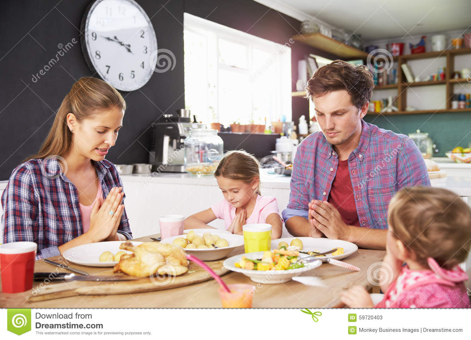 Famille disant la prière avant de manger le repas dans la cuisine ensemble