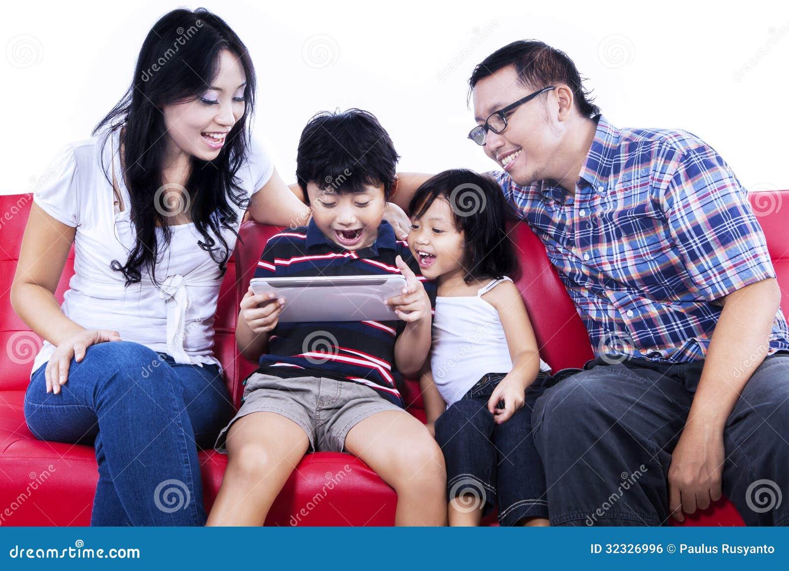 Famille enthousiaste jouant le jeu sur l Internet - d isolement