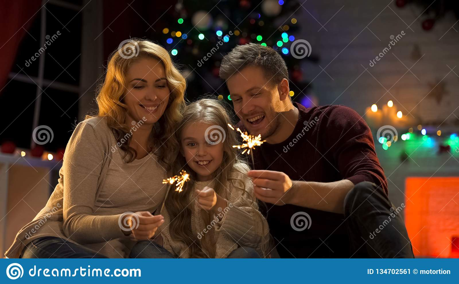 Famille enthousiaste tenant la lumière de Bengale se reposant sous l arbre de Noël, soirée du Nouveau an