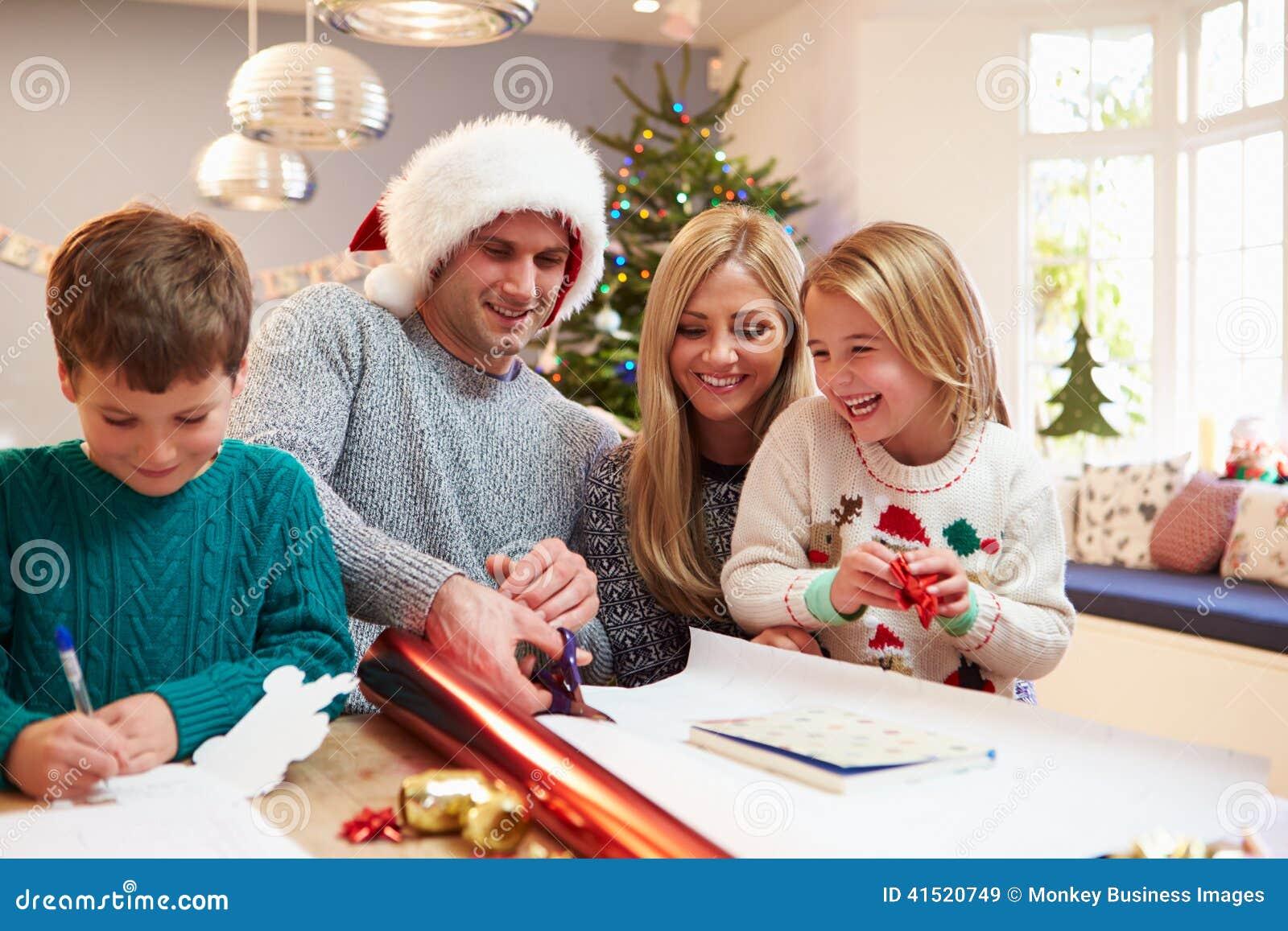 Famille enveloppant des cadeaux de Noël à la maison