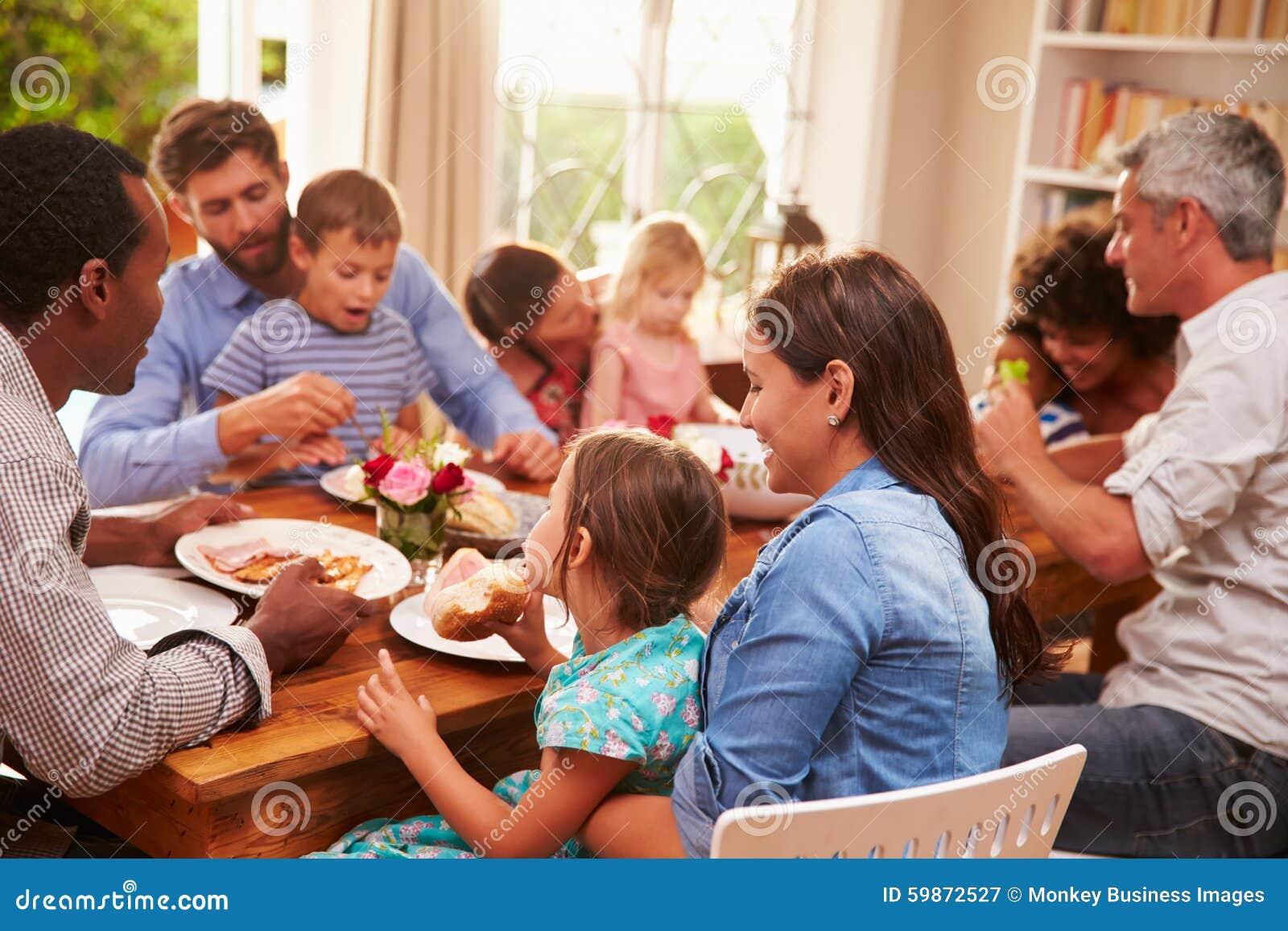 Famille et amis s asseyant à une table de salle à manger
