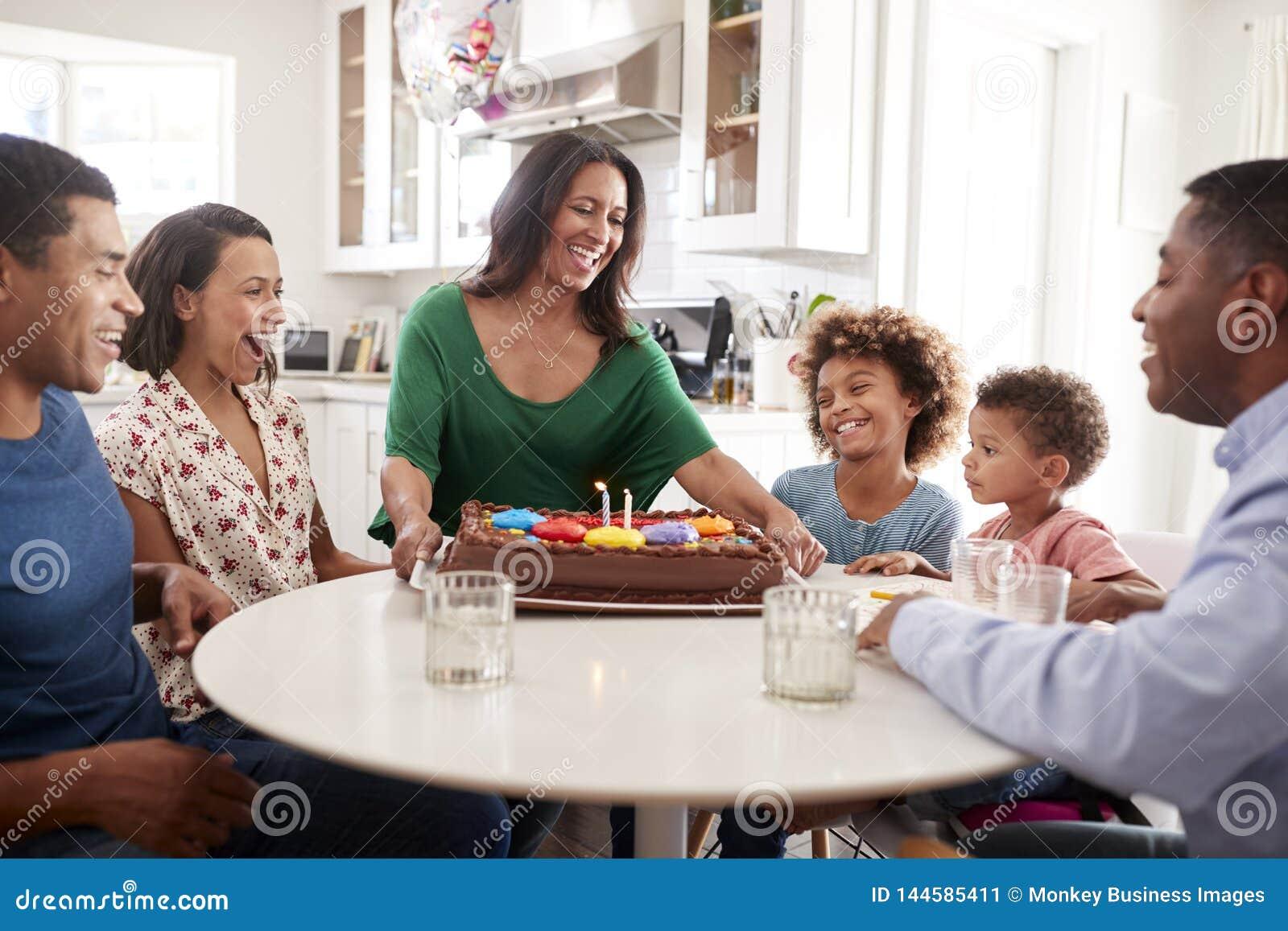 Famille excitée de trois générations se reposant ensemble dans la cuisine célébrant un anniversaire, grand-mère apportant le gâte