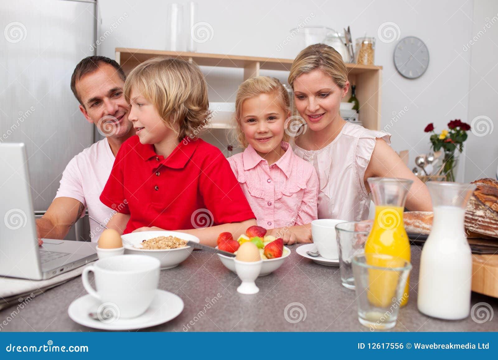 Famille gai prenant le petit déjeuner ensemble