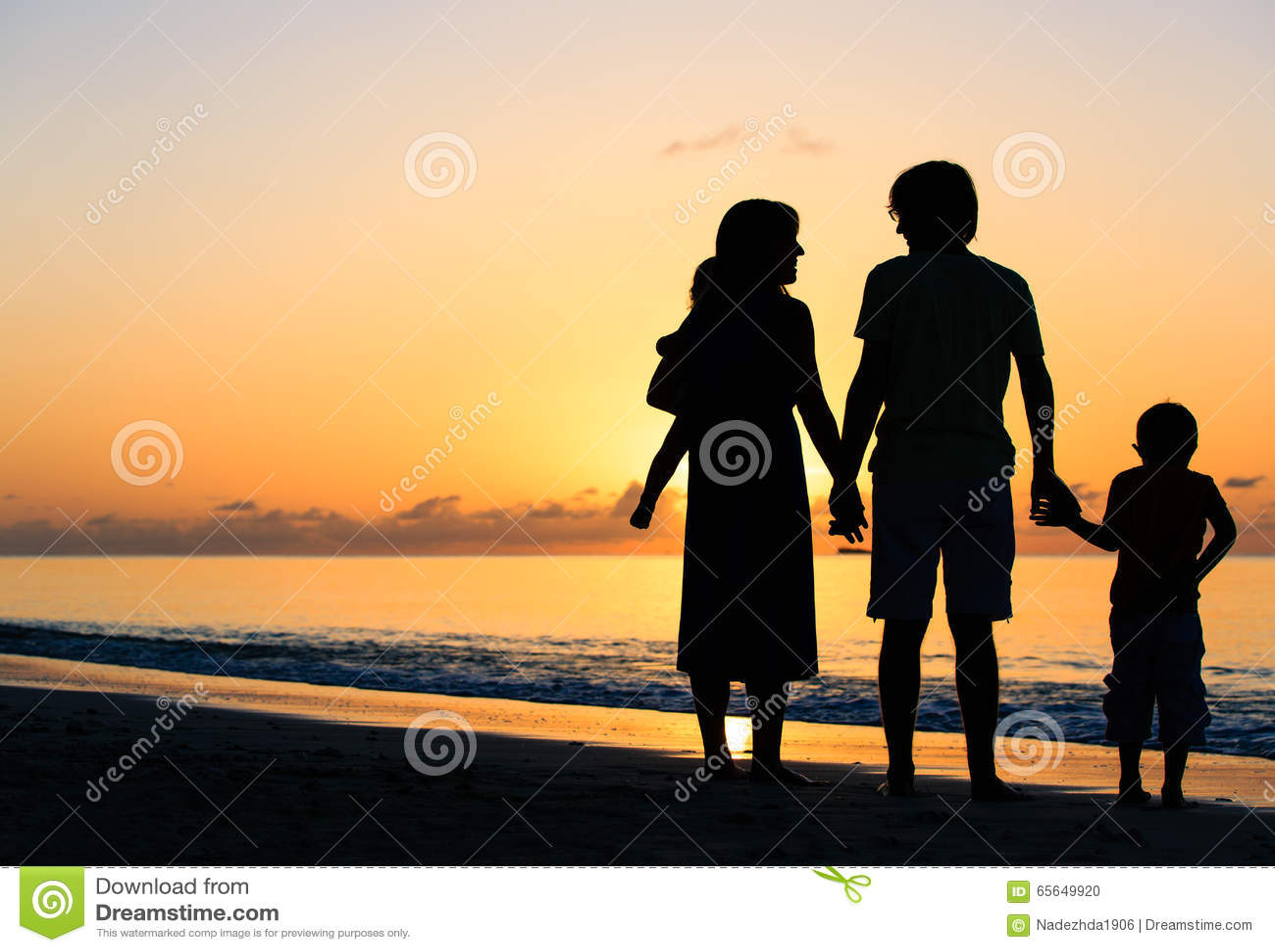Famille heureuse avec deux enfants sur la plage de coucher du soleil