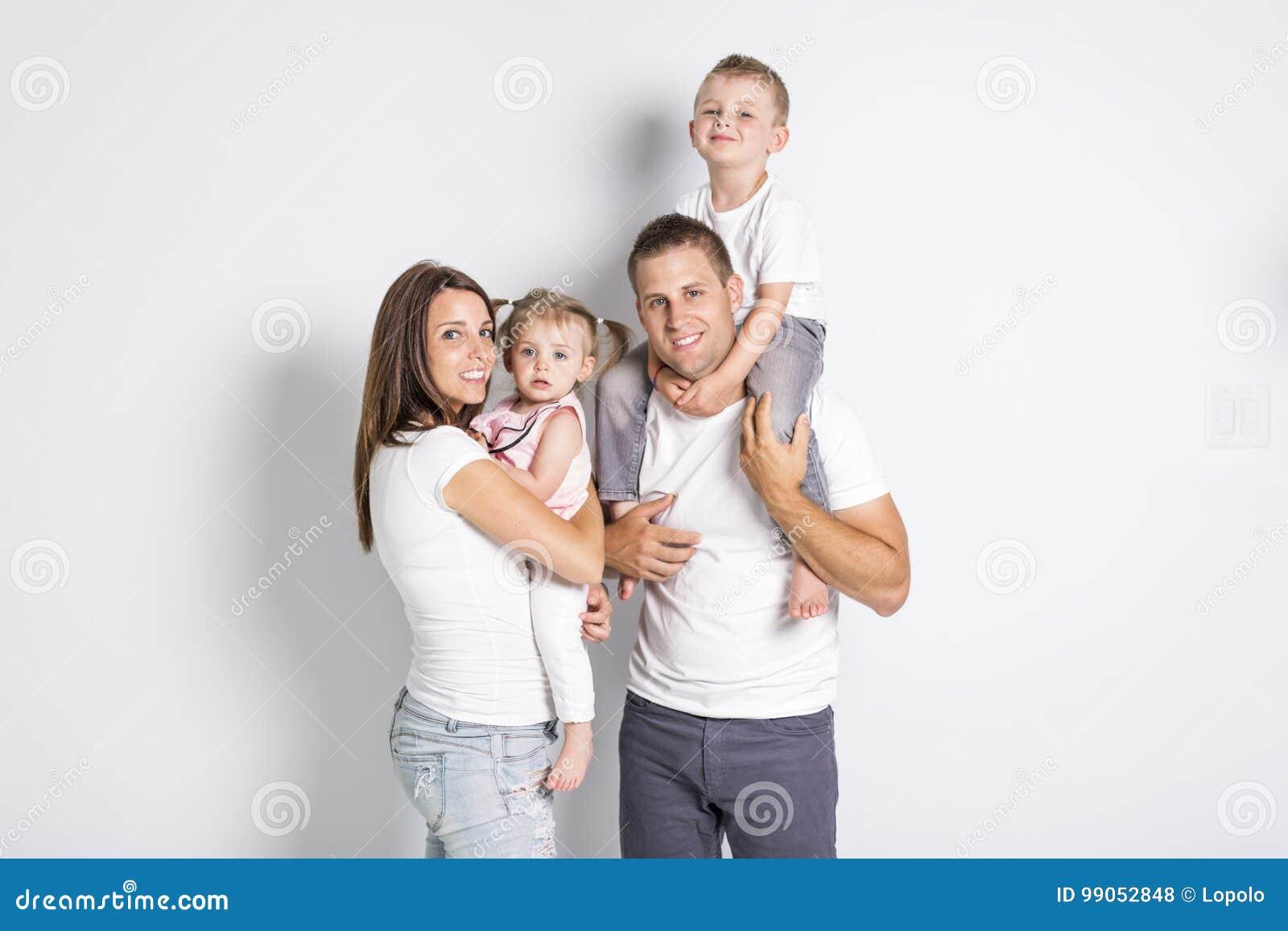 Famille heureuse avec deux enfants sur le fond de gris de studio