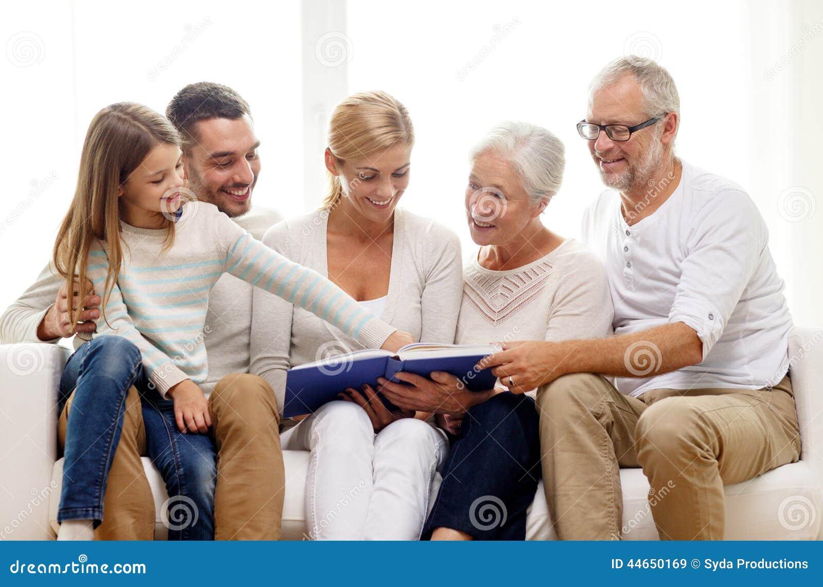 famille heureuse avec l 39 album photos de livre ou la maison photo stock image 44650169. Black Bedroom Furniture Sets. Home Design Ideas
