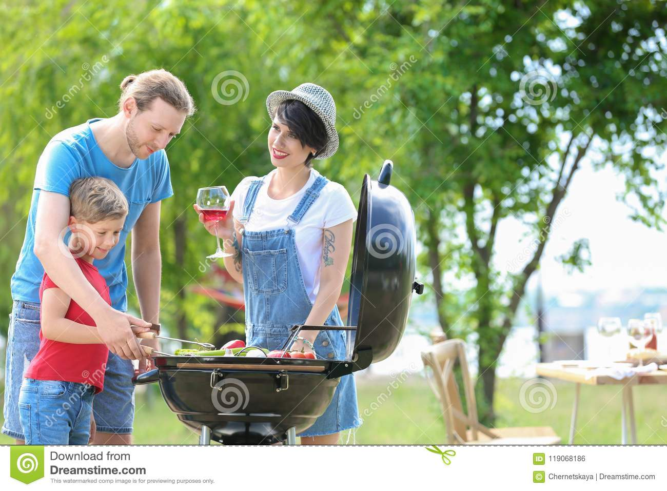 Famille heureuse ayant le barbecue avec le gril moderne