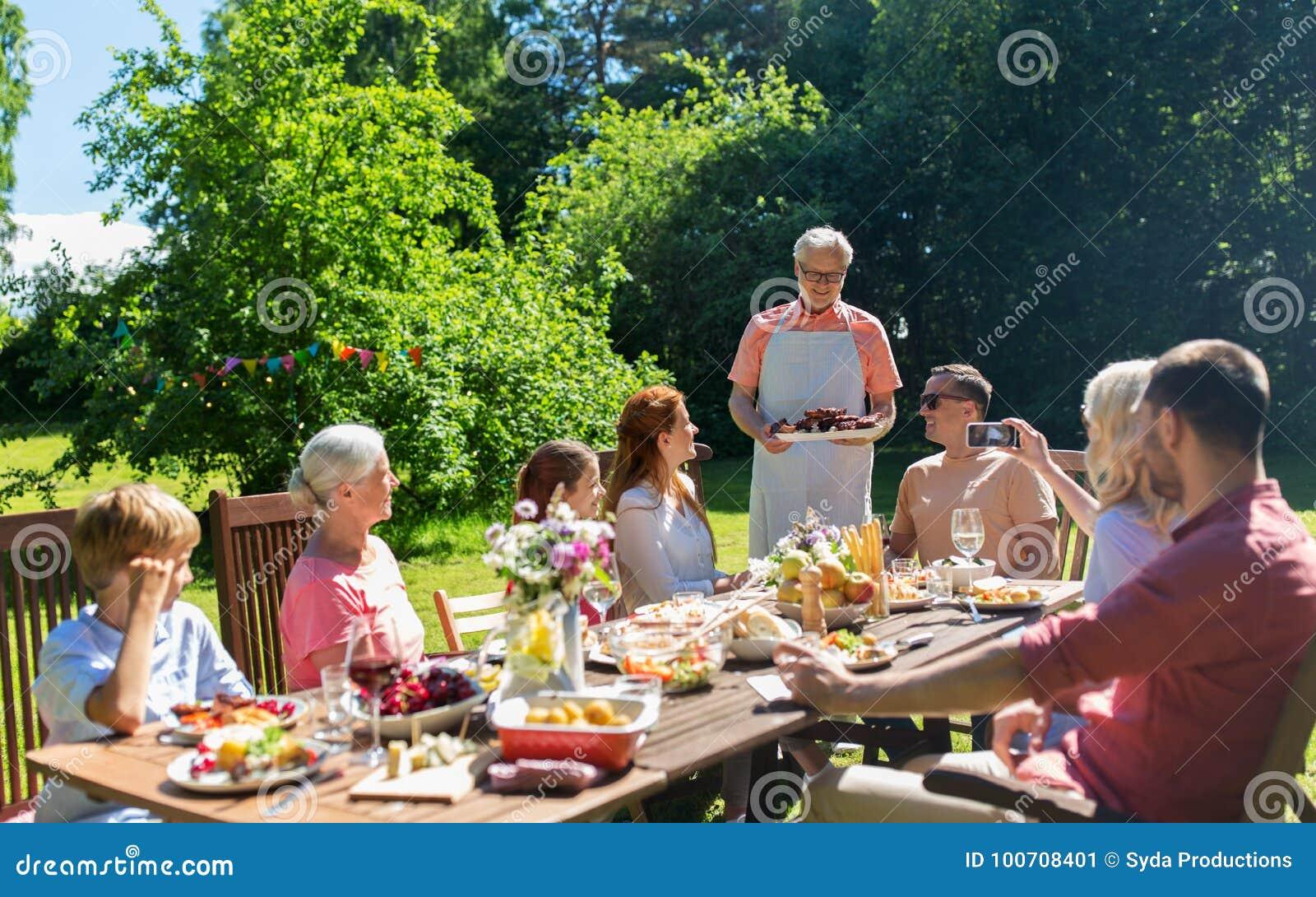 Famille heureuse ayant le dîner ou la réception en plein air d été