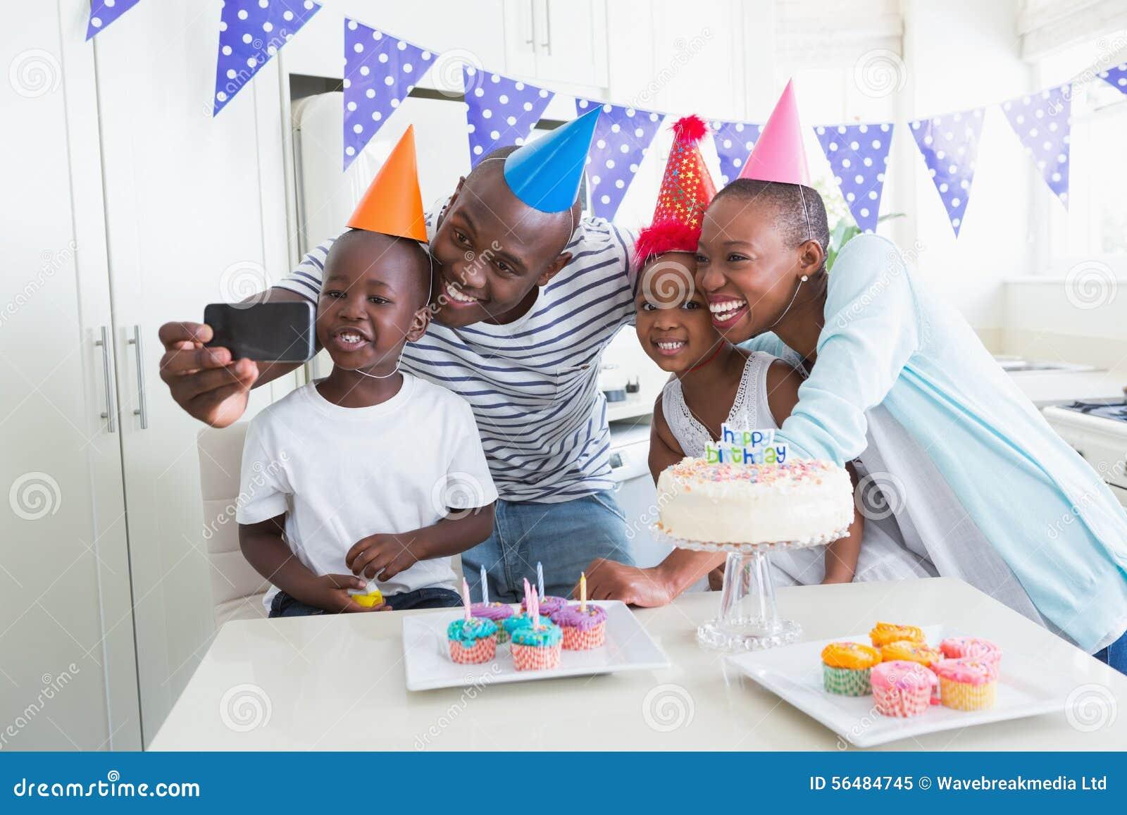 Famille heureuse célébrant un anniversaire ensemble et prenant un selfie