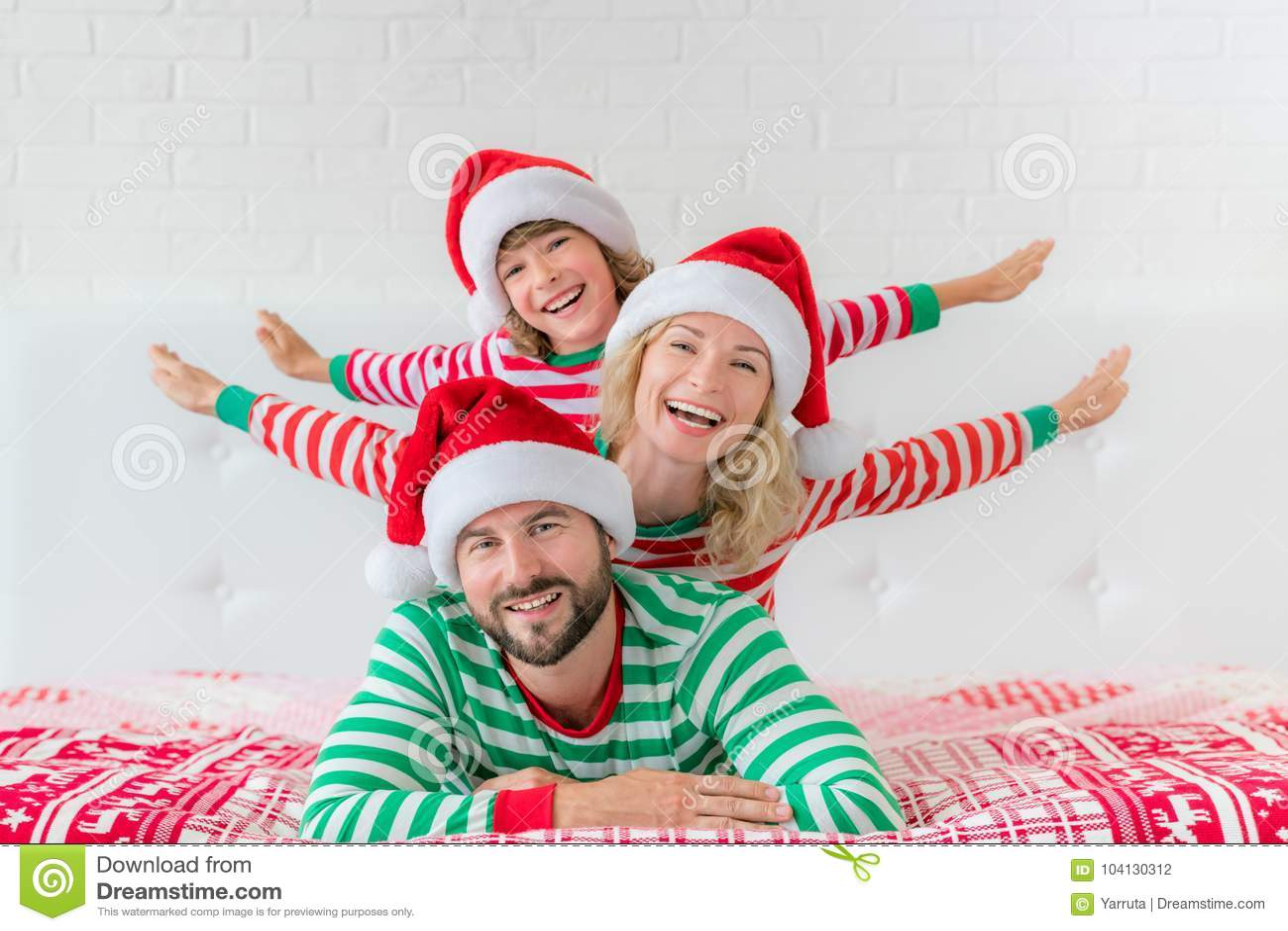 4e53954dc615d Famille heureuse utilisant des chapeaux de Santa Claus se trouvant sur le  lit Mère   père et enfant ayant l amusement dans le temps de Noël Homme