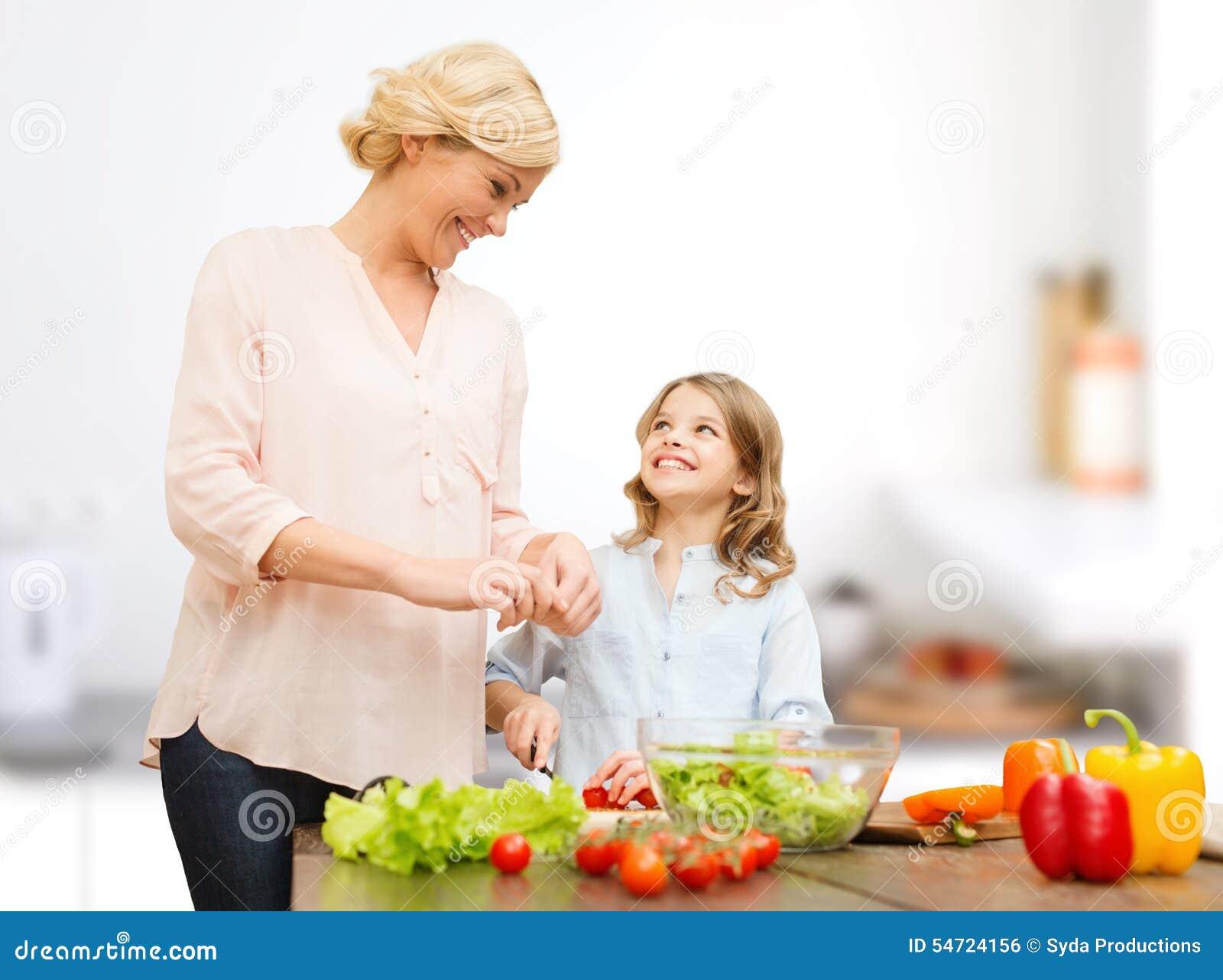 Famille heureuse faisant cuire la salade végétale pour le dîner