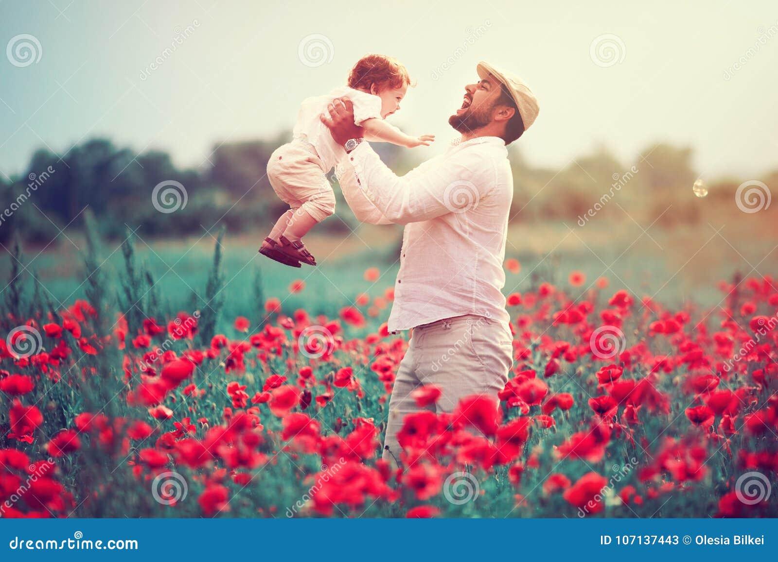 Famille heureuse, père avec le bébé garçon infantile jouant dans le domaine de fleur de pavot au jour d été