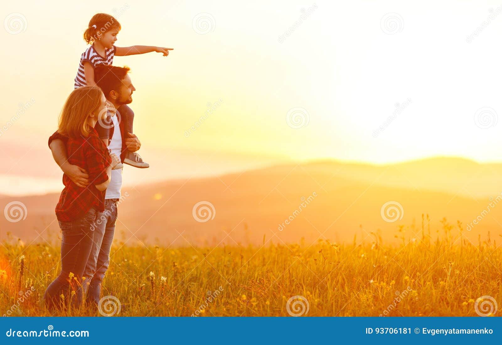 Famille heureuse : père de mère et fille d enfant sur le coucher du soleil