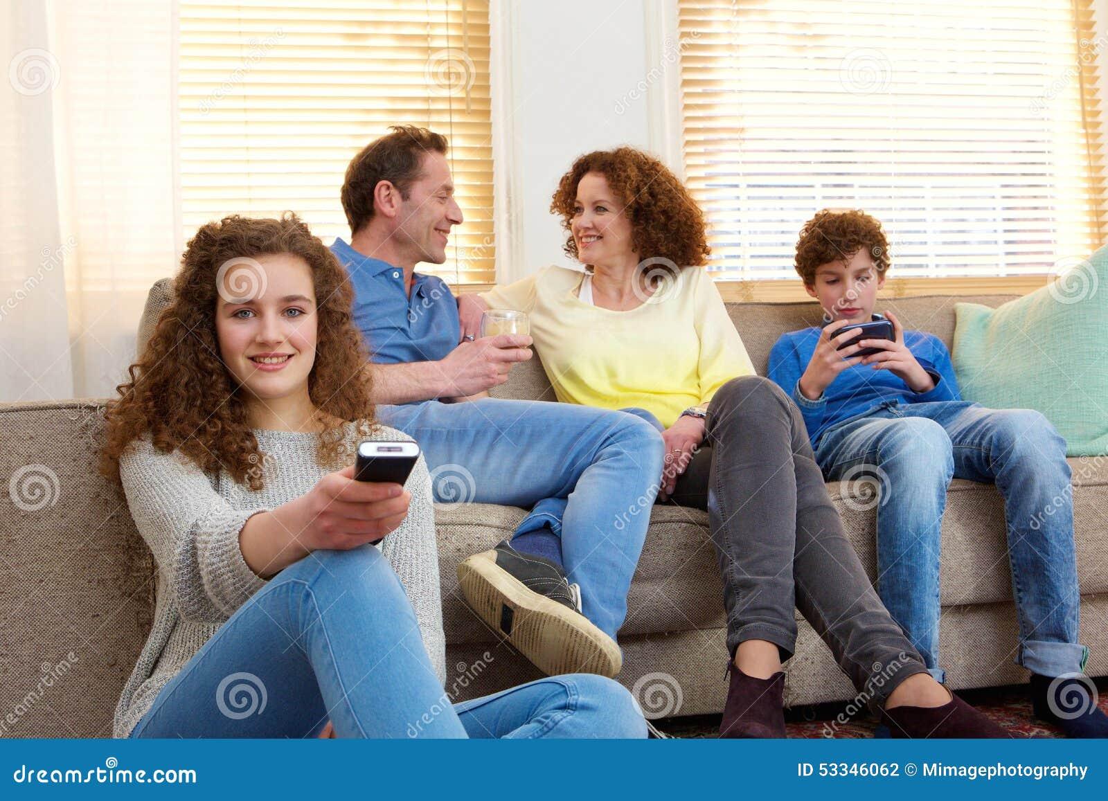 famille heureuse reposant la maison la d tente dans le salon photo stock image 53346062. Black Bedroom Furniture Sets. Home Design Ideas