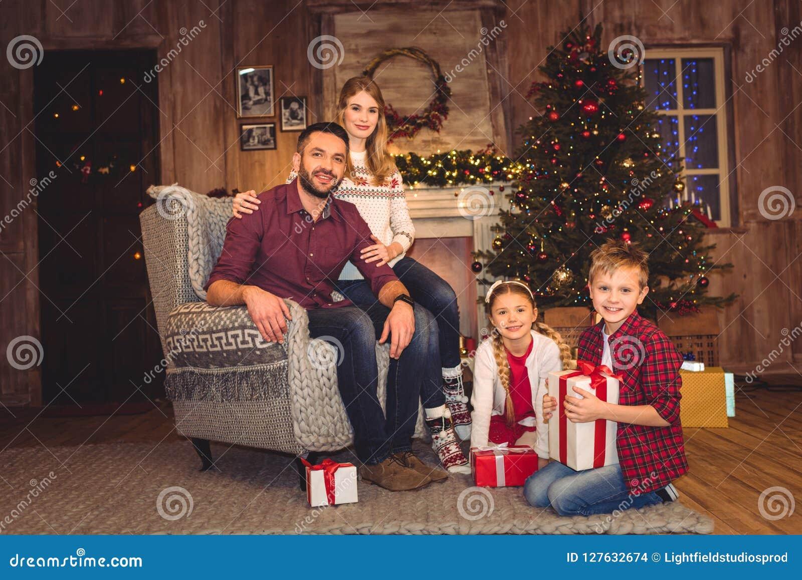 Famille heureuse s asseyant avec des cadeaux de Noël et le regard