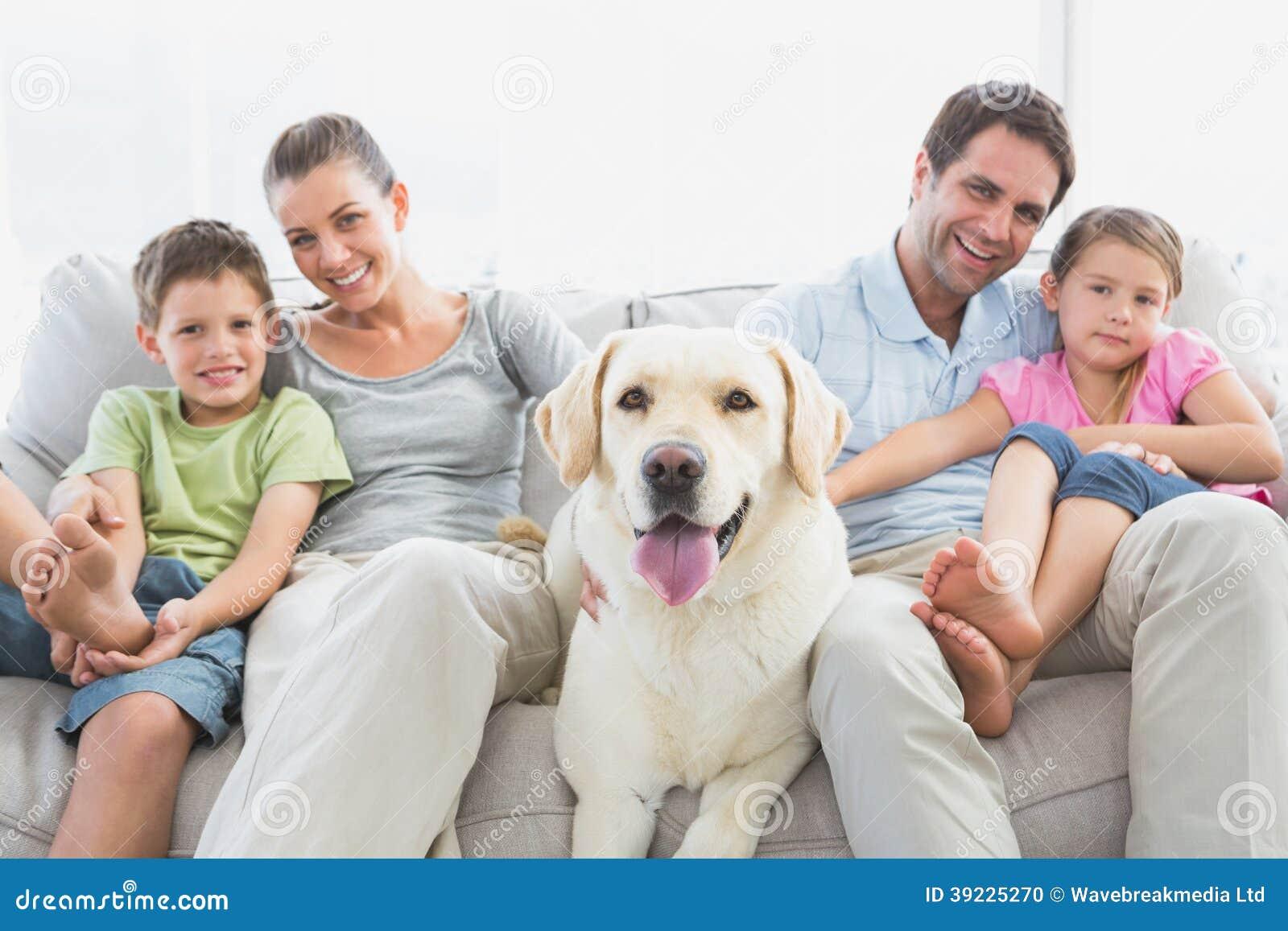 famille heureuse s 39 asseyant sur le divan avec leur animal familier labrador photo stock image. Black Bedroom Furniture Sets. Home Design Ideas