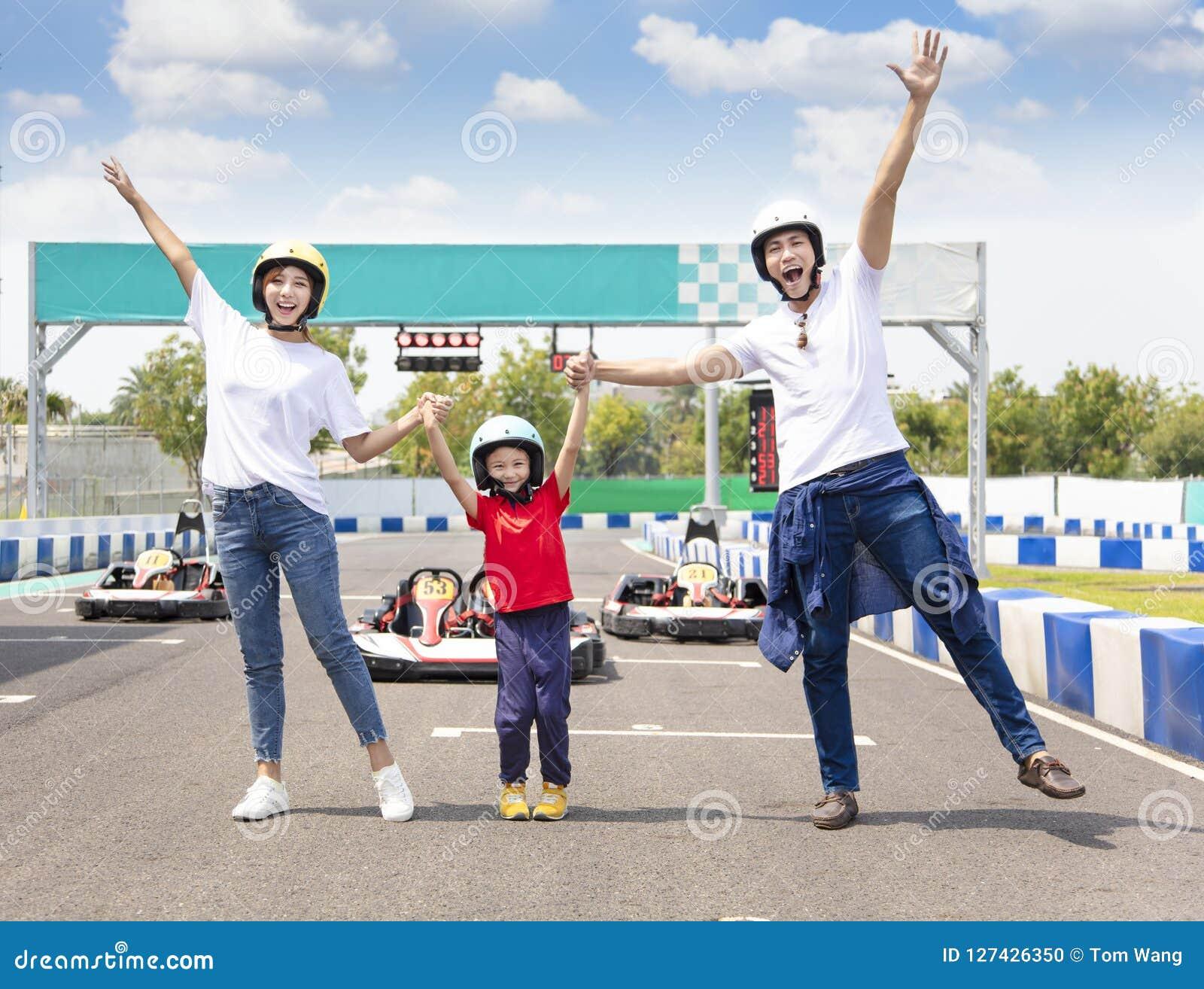Famille heureuse se tenant sur la voie de course de kart d aller