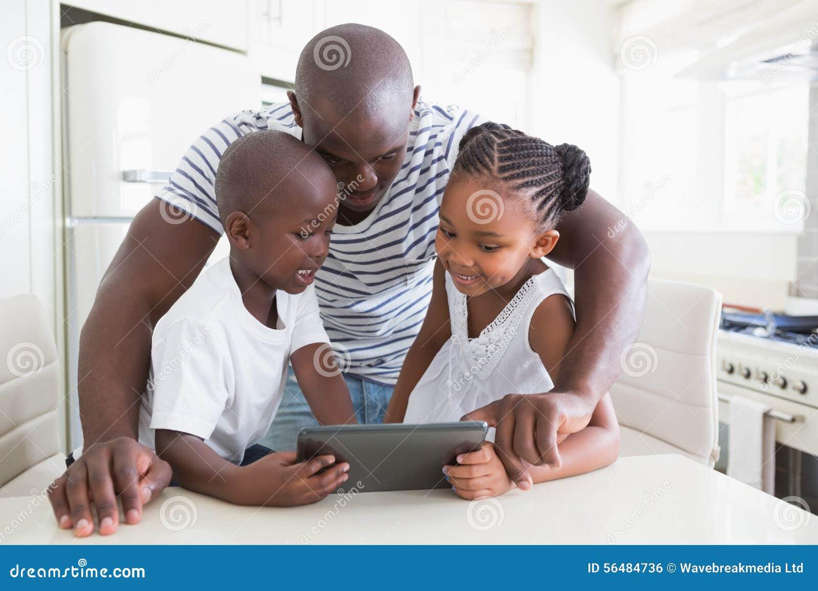 Famille heureuse sur la table avec le comprimé numérique