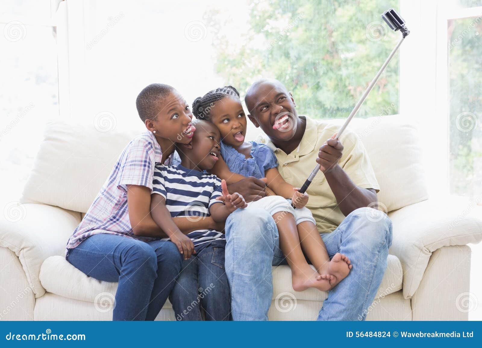 Famille heureuse sur le divan prenant un selfie