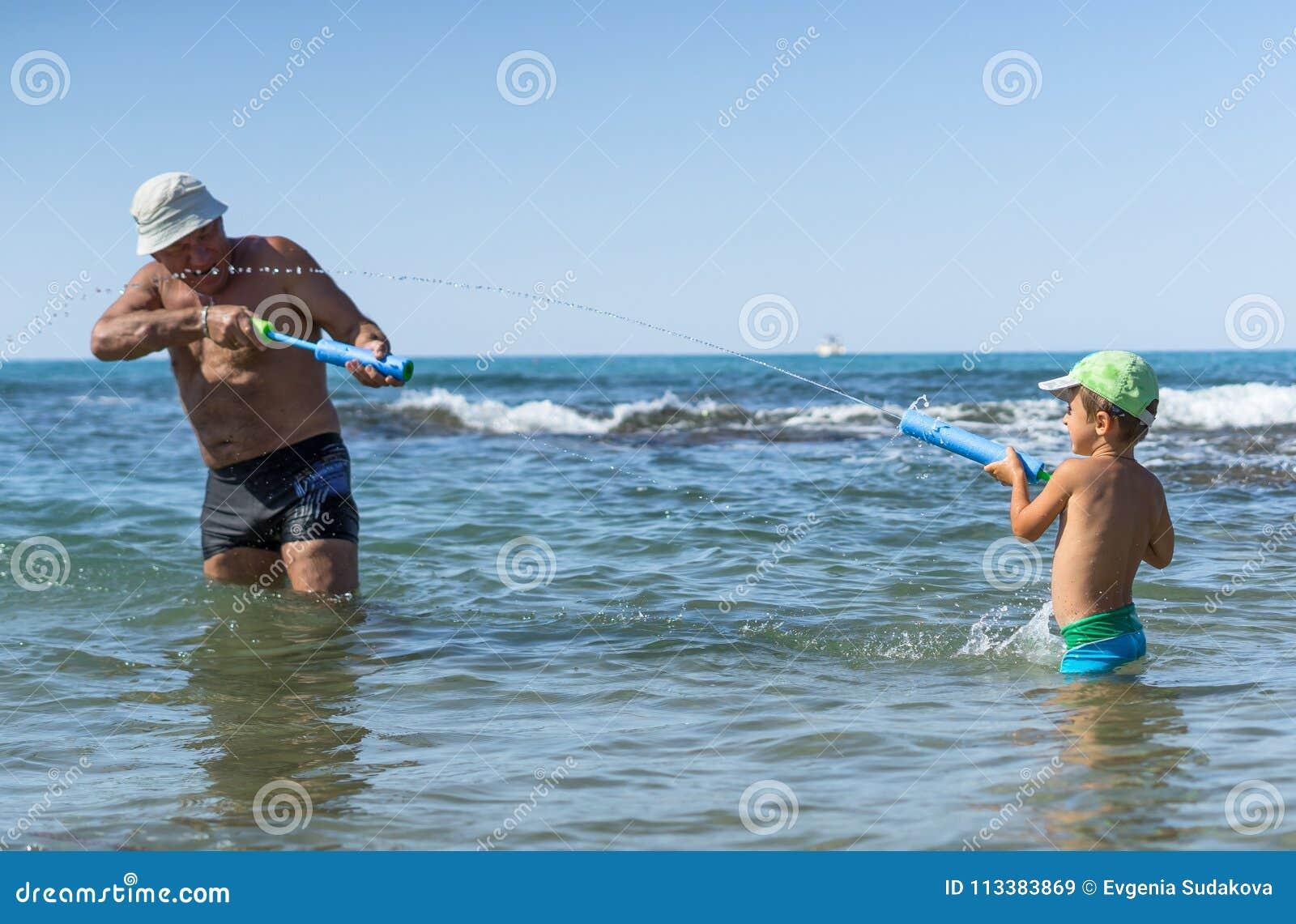 Famille heureux Grand-père et petit-fils de sourire jouant à la mer Émotions humaines positives, sentiments, joie À la plage de F