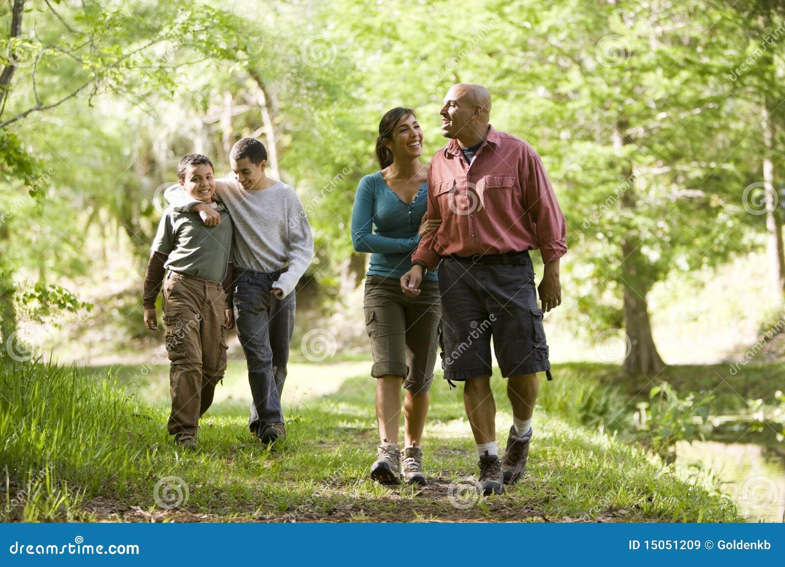 Famille hispanique marchant le long du journal en stationnement