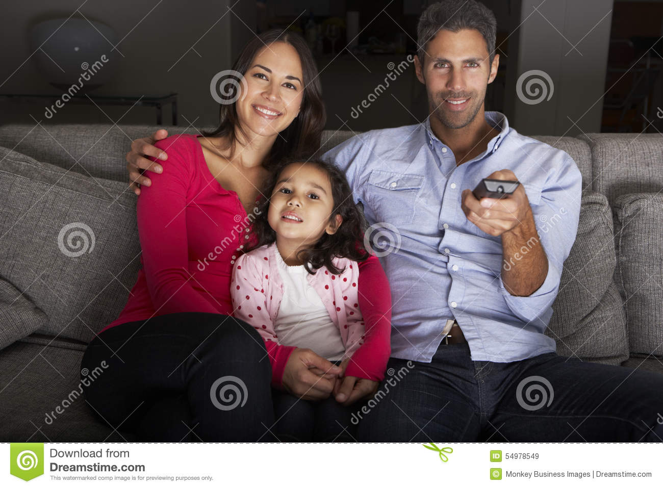 Famille hispanique s asseyant sur Sofa And Watching TV