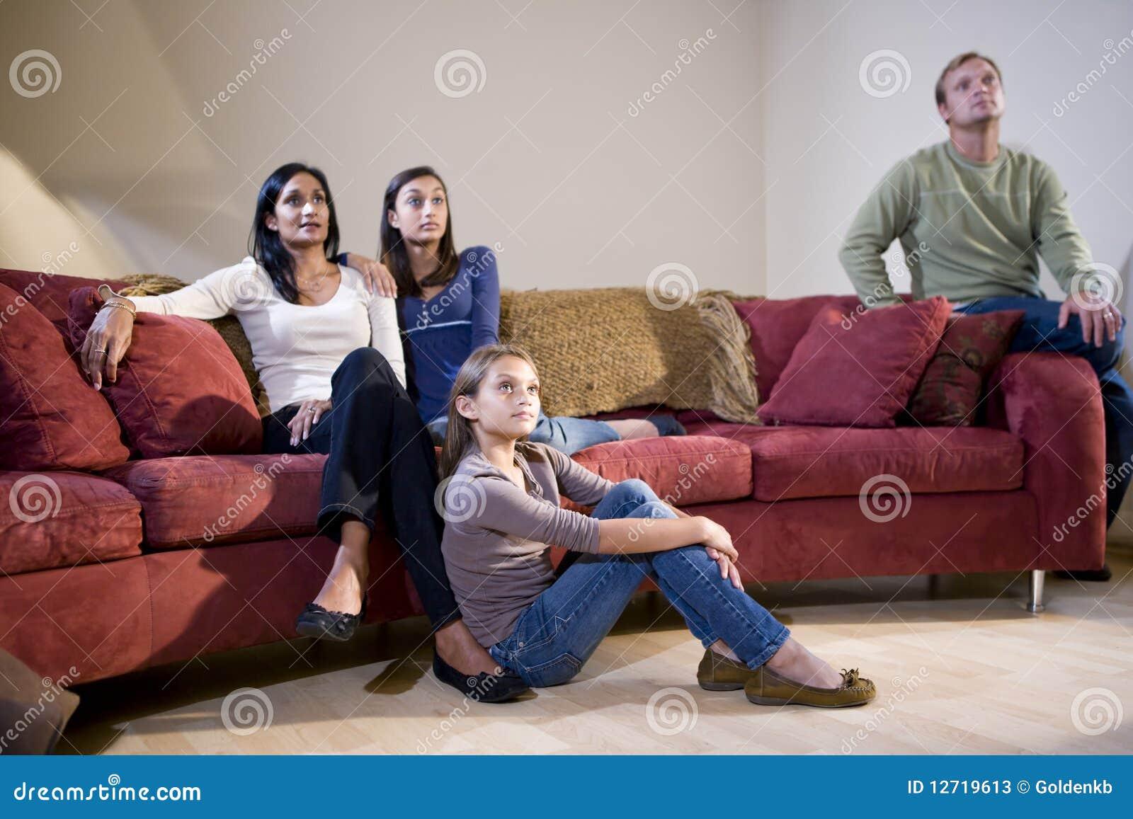 Famille interracial s asseyant sur le sofa regardant la TV