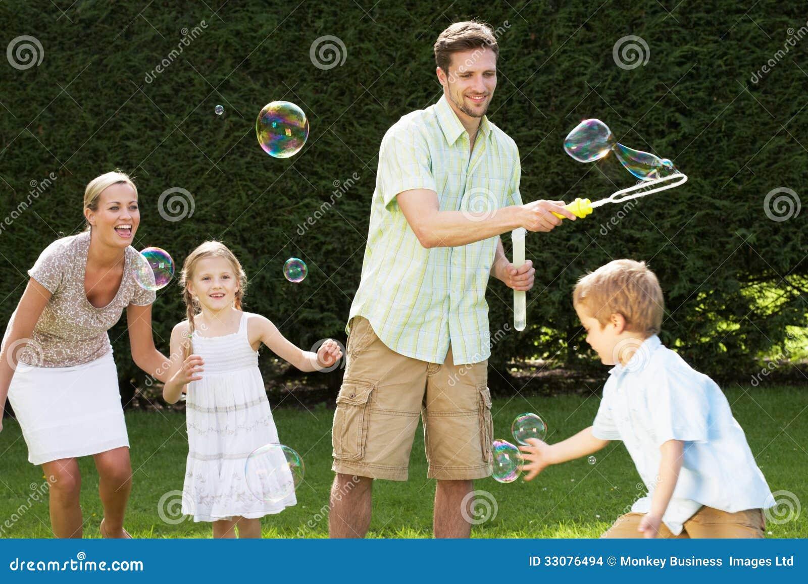 Famille jouant avec des bulles dans le jardin photo stock - Bulle de jardin prix ...