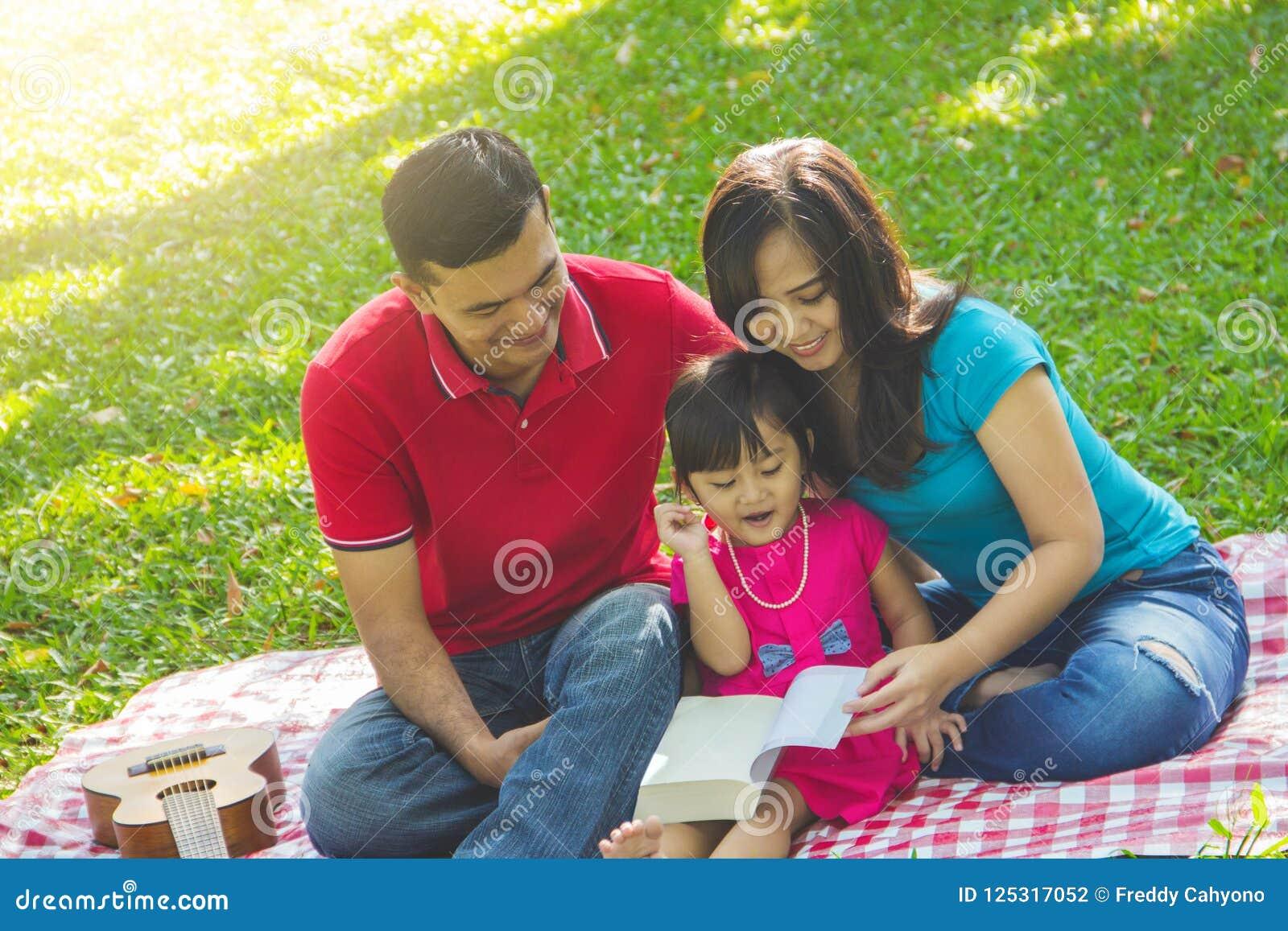 Famille lisant un livre ensemble en nature
