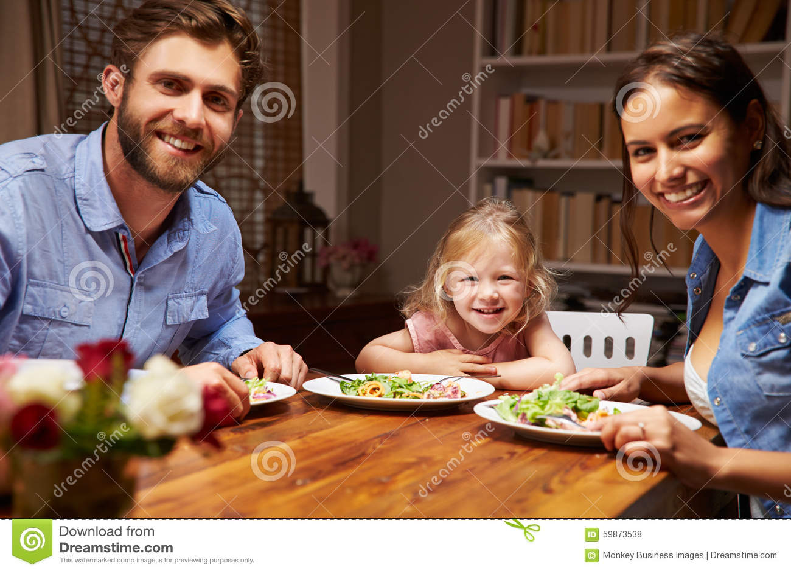 Famille mangeant le dîner à une table de salle à manger, regardant l appareil-photo