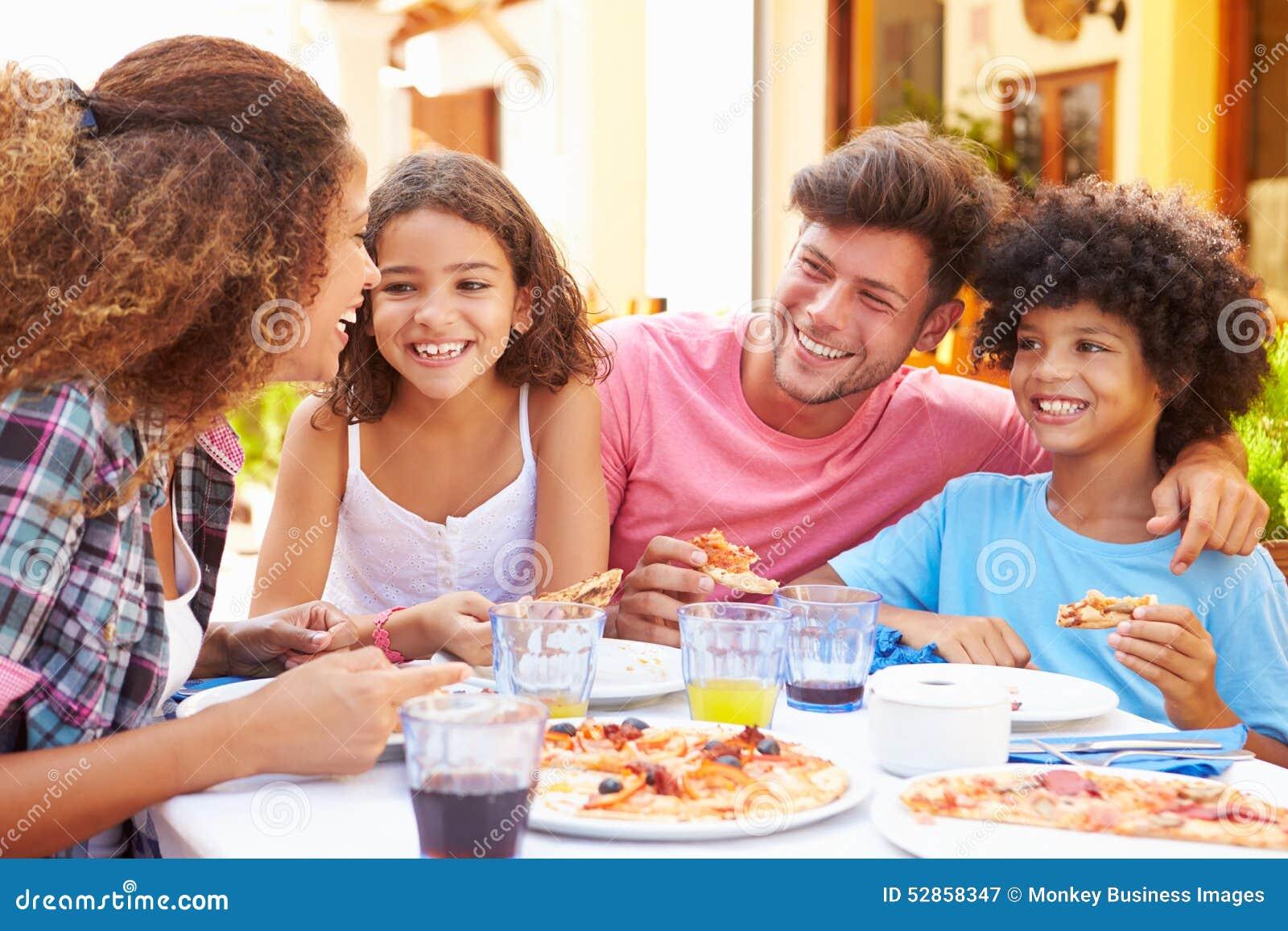 Famille mangeant le repas au restaurant extérieur ensemble