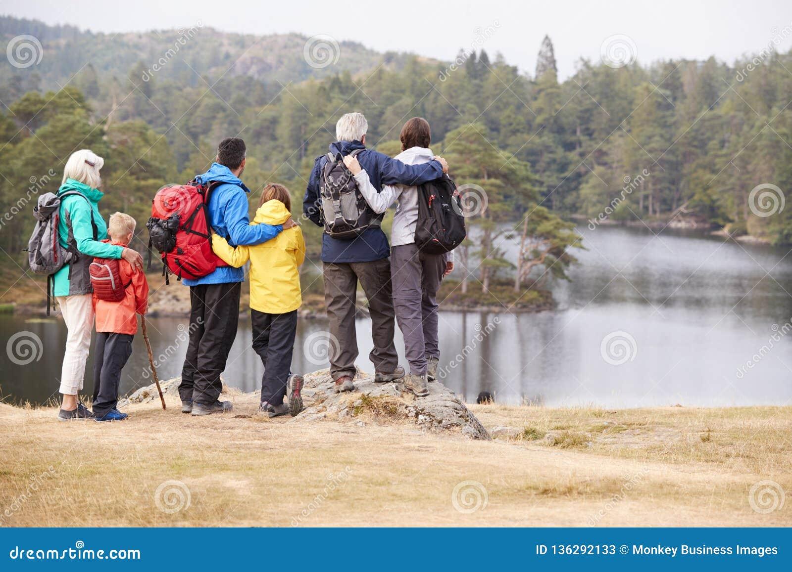 Famille multi de génération embrassant et admirant la vue de bord de lac, vue arrière, secteur de lac, R-U