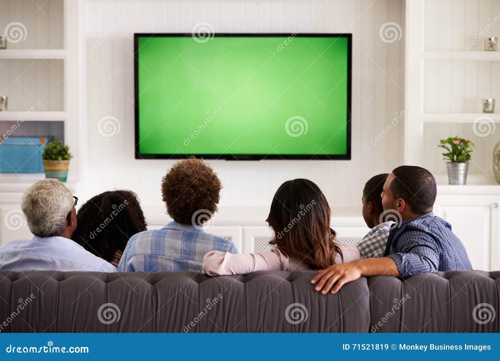 Famille Multi De Generation Regardant La Tv A La Maison Vue Arriere