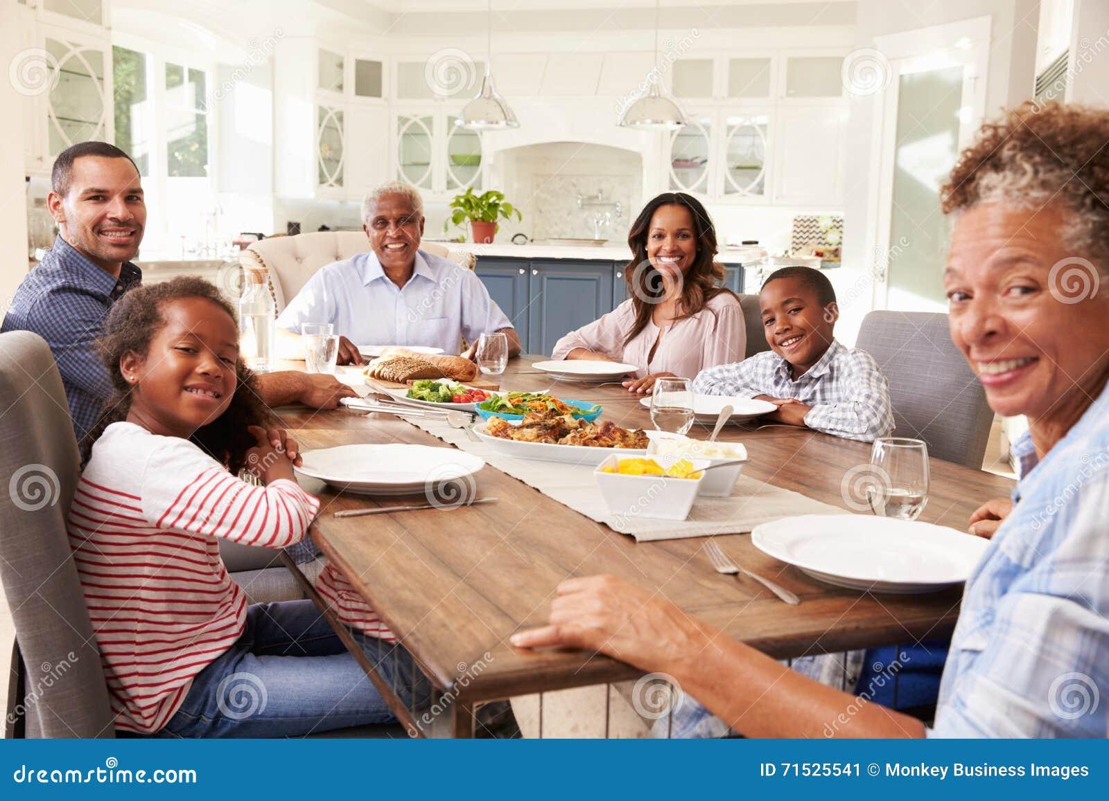Famille multi de noir de génération à la table de cuisine pour un repas