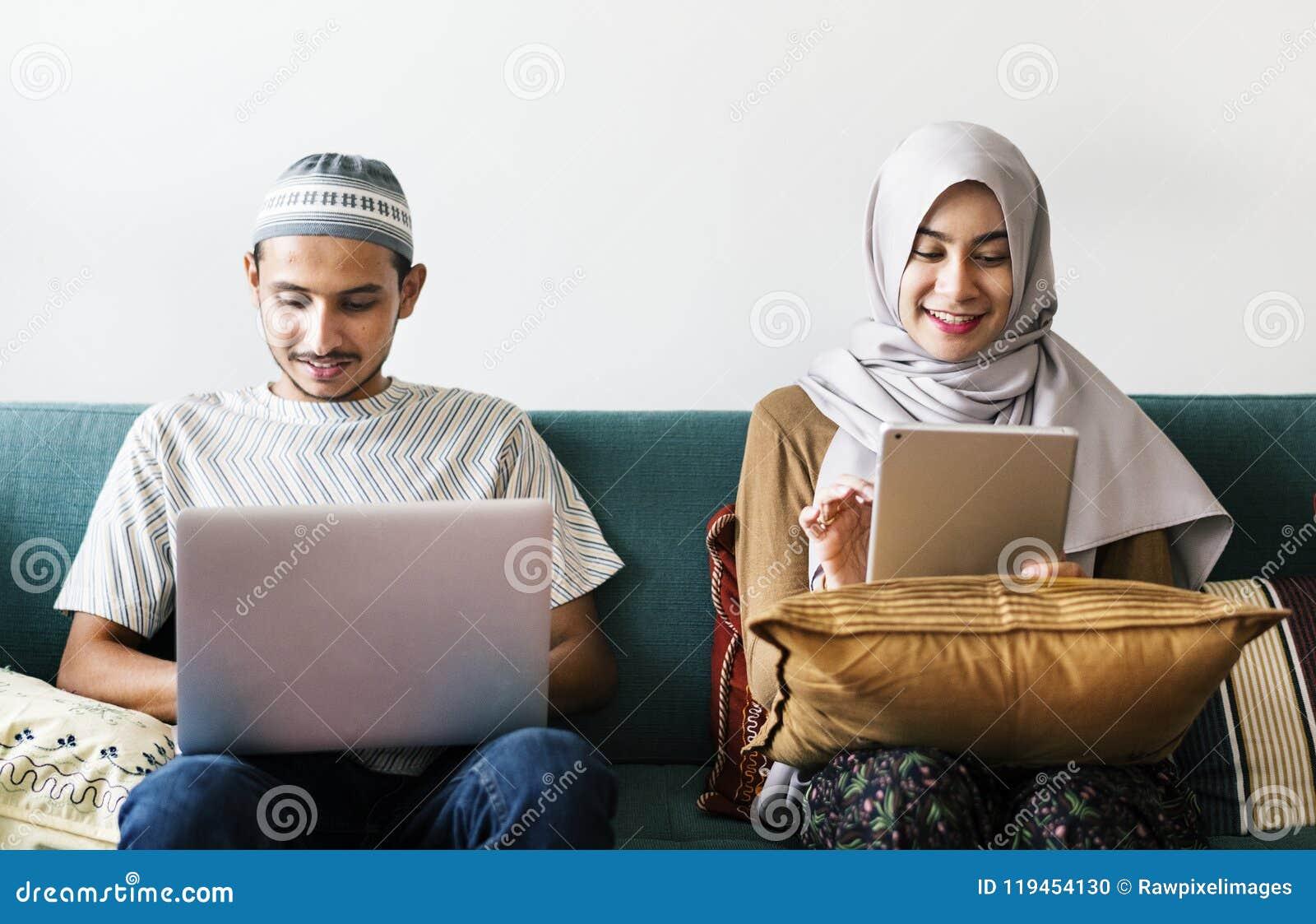 Famille musulmane utilisant les dispositifs numériques à la maison