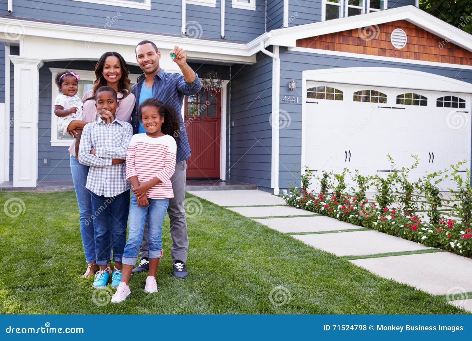 Famille noire heureuse debout en dehors de leur maison, papa tenant la clé