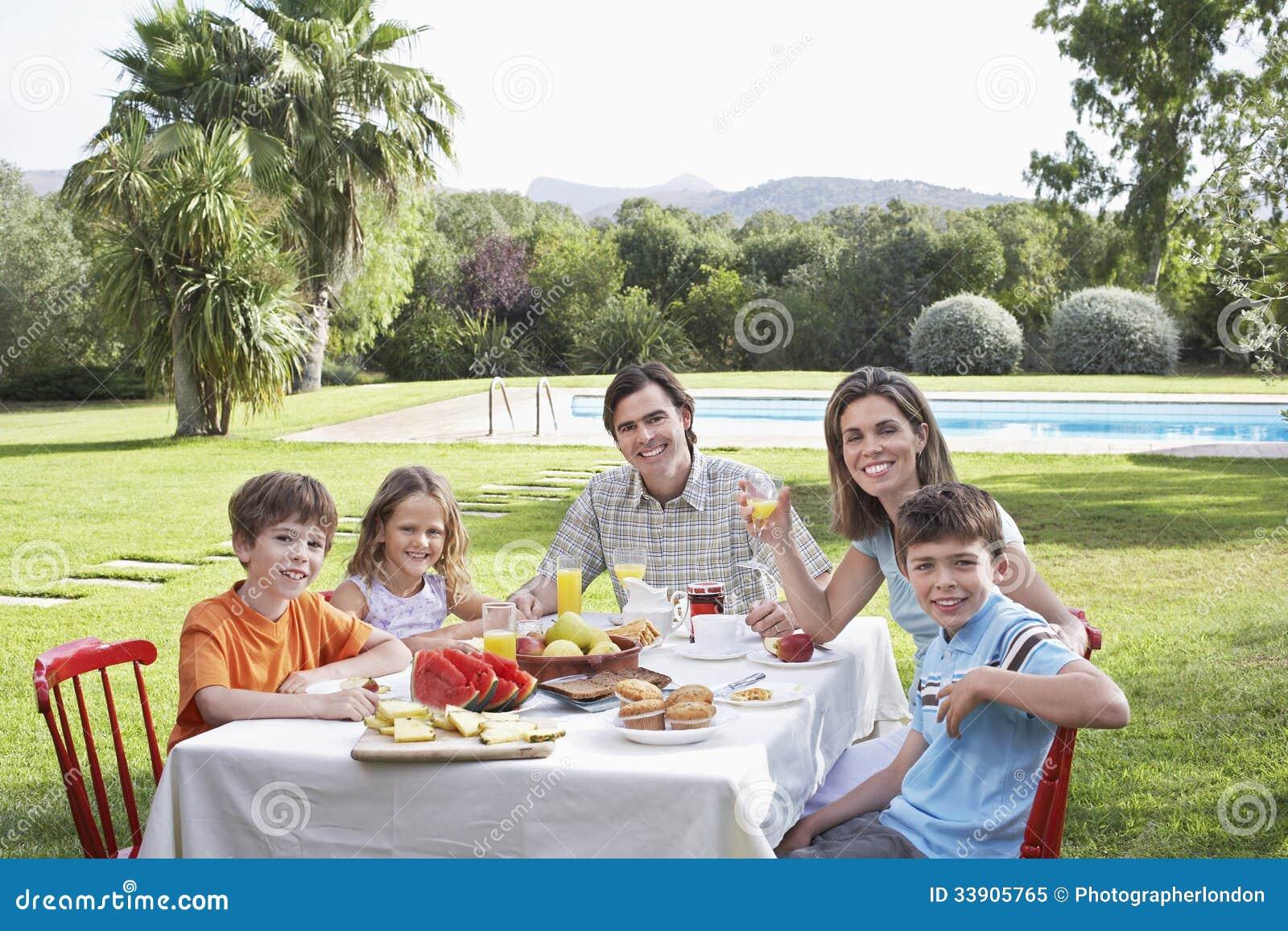 Famille s 39 asseyant au tableau de petit d jeuner dans le for Au jardin de la famille de fabreville