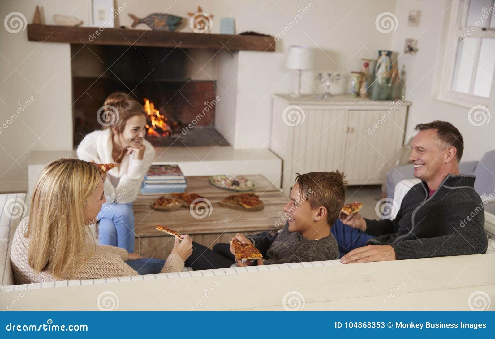 Famille s asseyant sur le feu ouvert de Sofa In Lounge Next To mangeant de la pizza