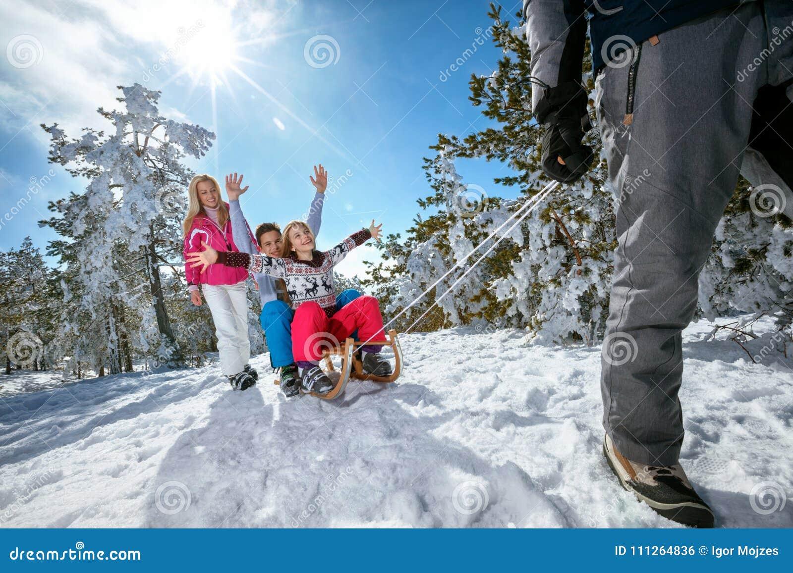 Famille sur la neige sledding et appréciant le jour ensoleillé d hiver