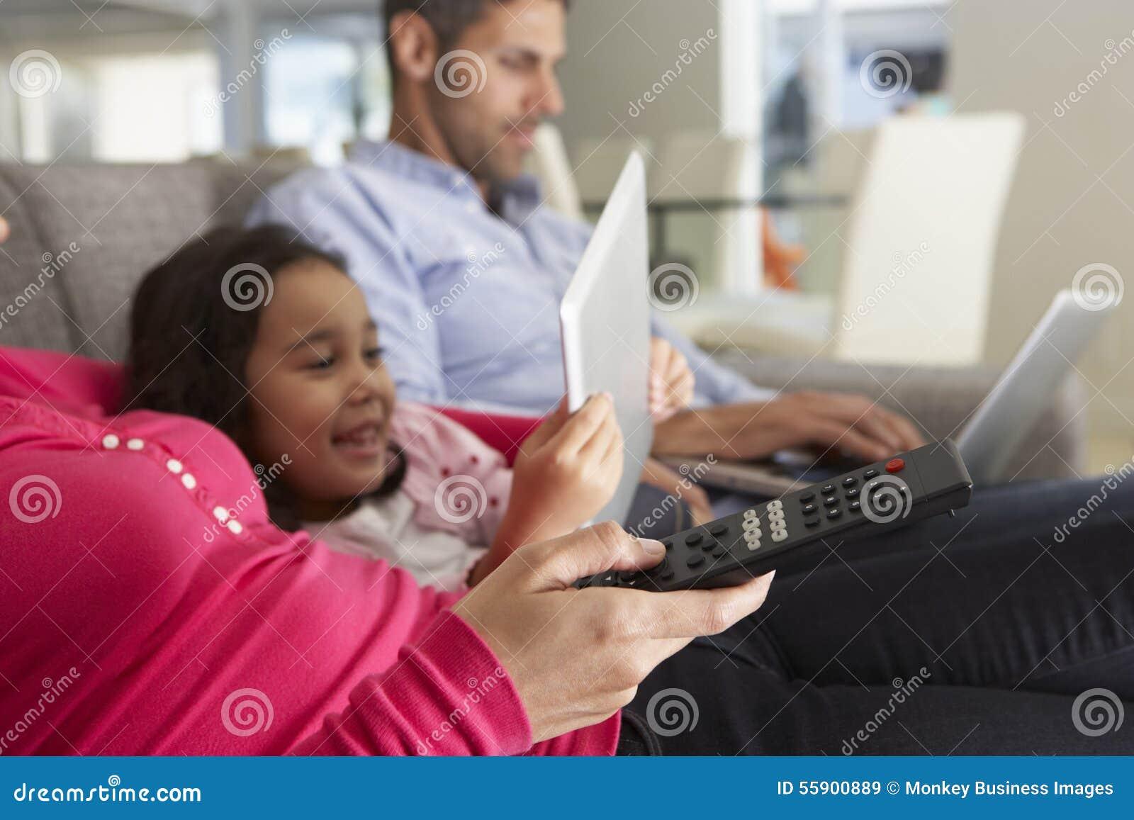 Famille sur la Tablette de Sofa With Laptop And Digital regardant la TV