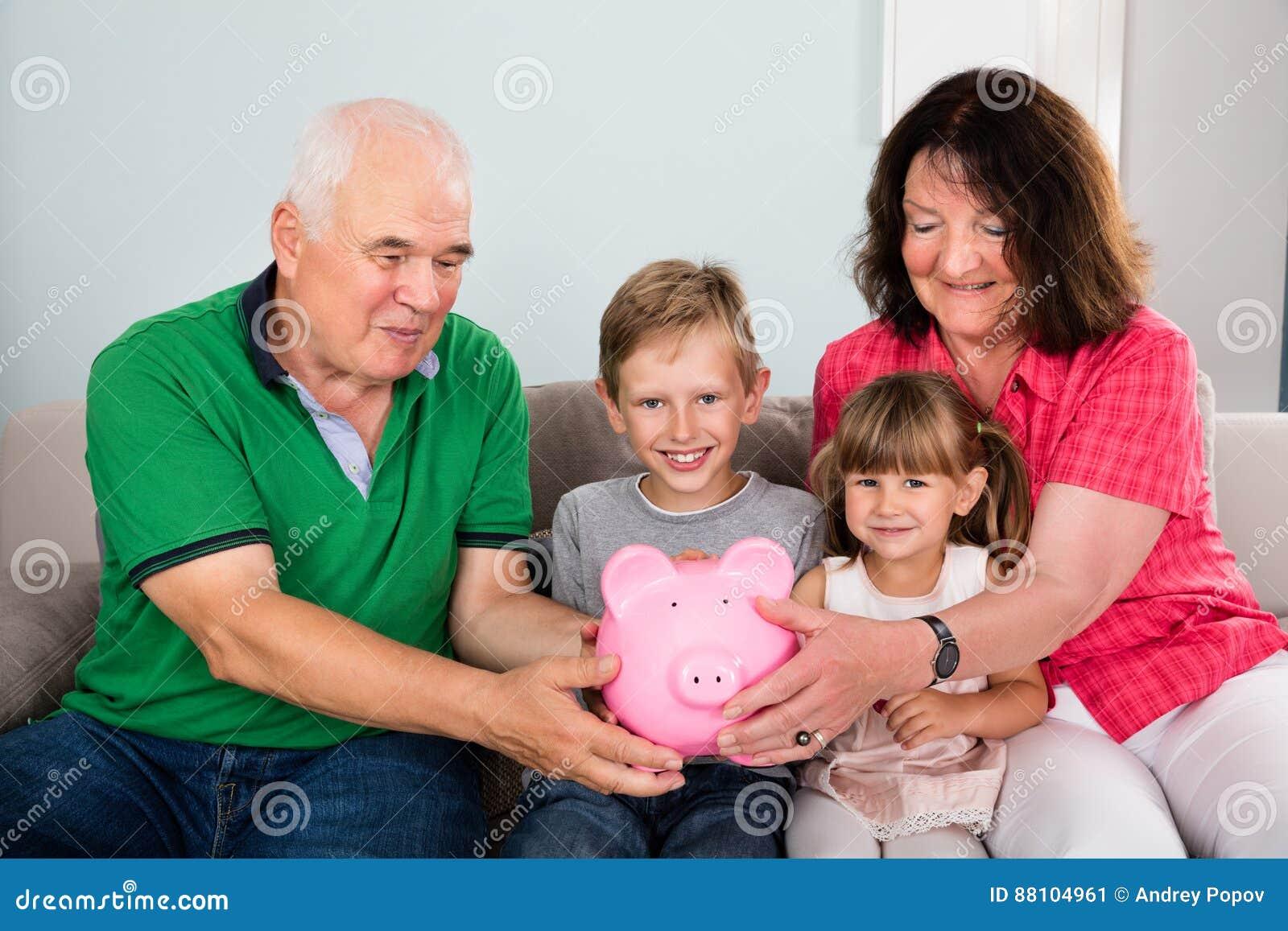 Famille tenant la tirelire à la maison