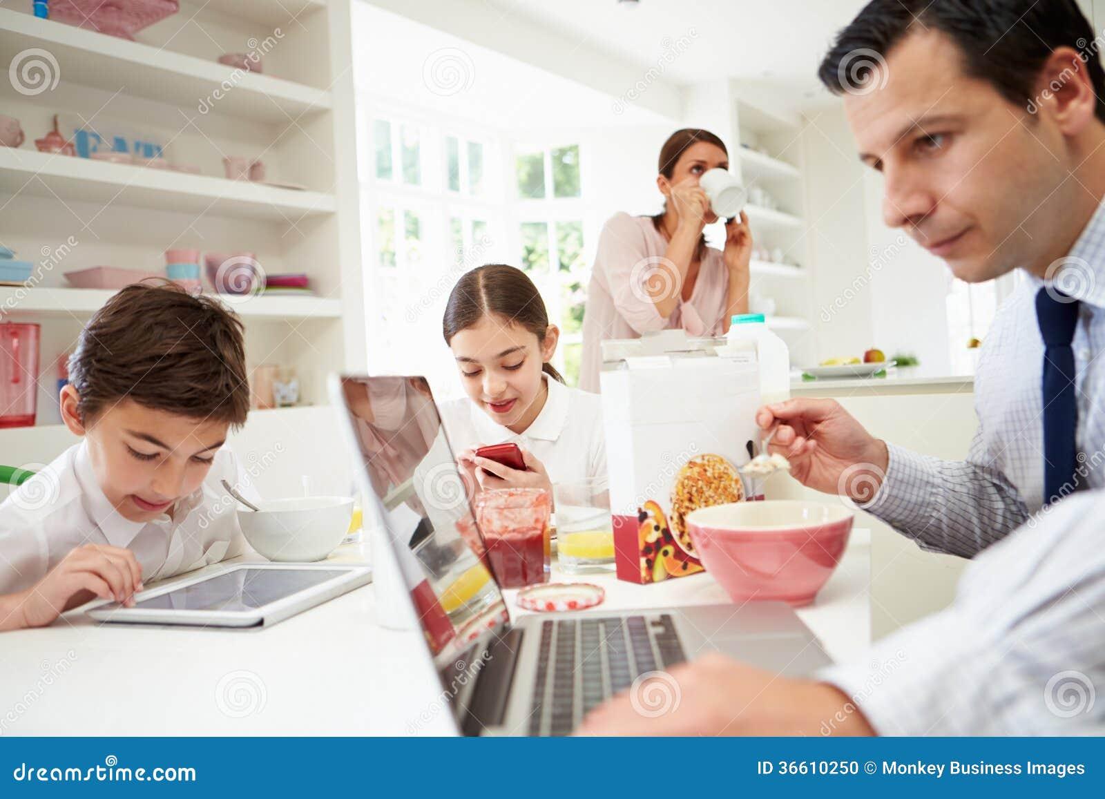 Famille utilisant des dispositifs de Digital au Tableau de petit déjeuner