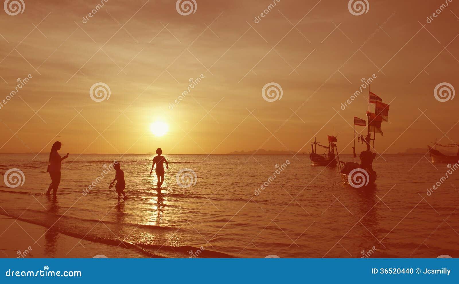 Familly détendent tandis que coucher du soleil par la plage