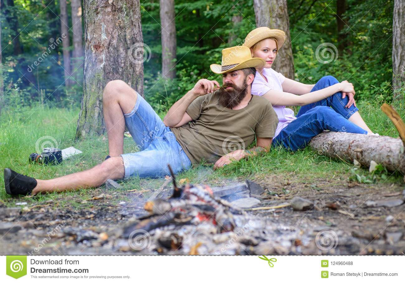 Family activity for summer vacation in forest and nature. Family relaxing near bonfire after day of mushroom hunting