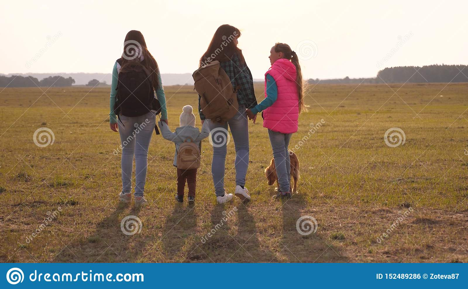 Family with backpacks travels with a dog. teamwork of a close-knit family. mother, daughters and home pets tourists