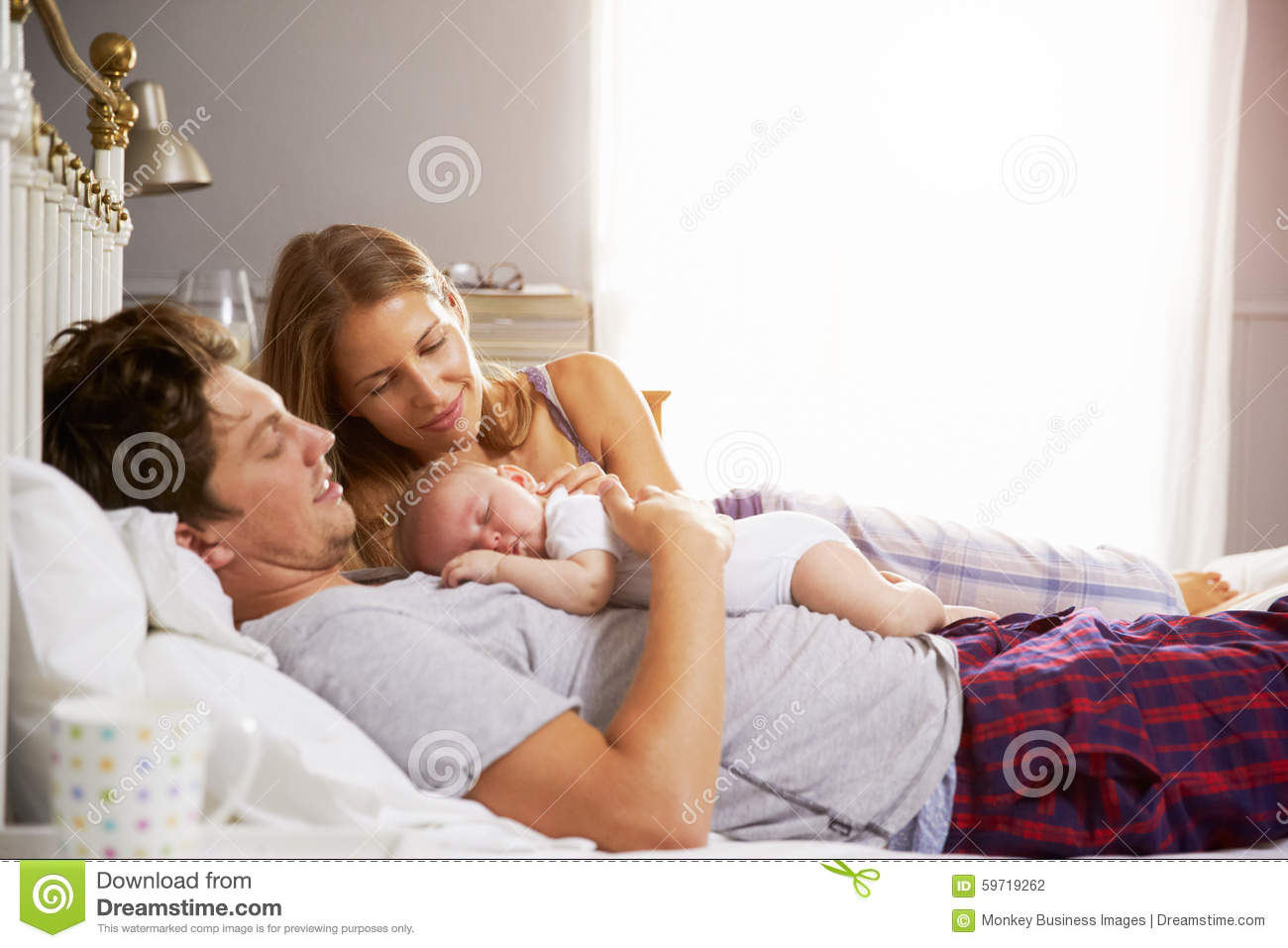 Family In Bed Holding Sleeping Newborn Baby Daughter Stock