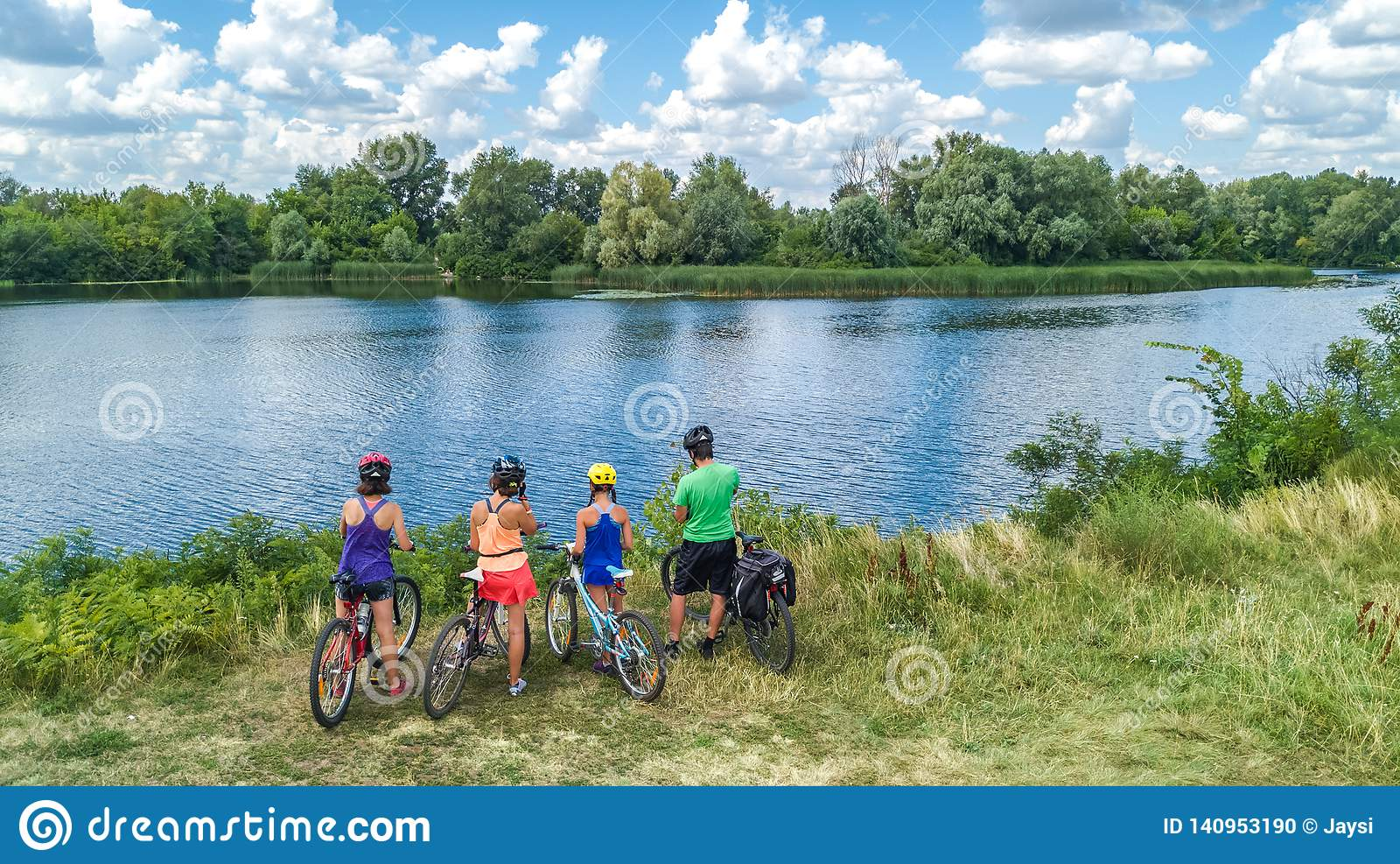 Family on bikes cycling outdoors, active parents and kids on bicycles, aerial view of happy family with children relaxing