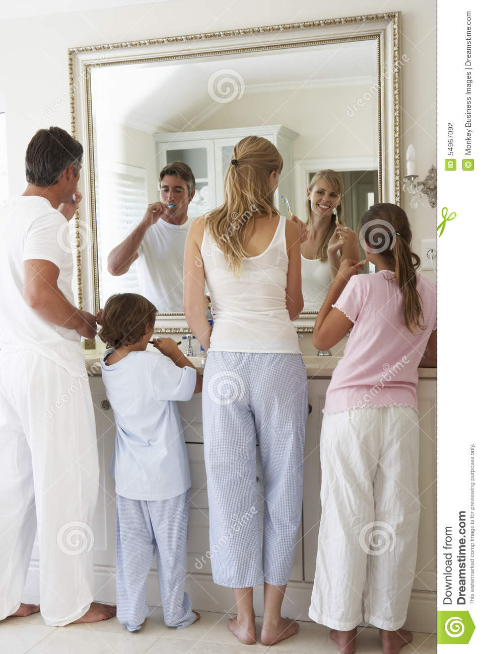 Family Brushing Teeth In Bathroom Mirror Stock Photo